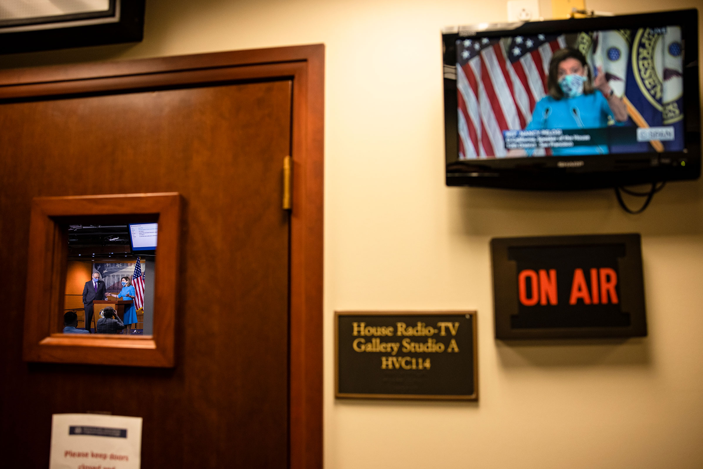 The broadcast of the press conference with Speaker of the House Nancy Pelosi and Senate Minority Leader Chuck Schumer is seen on a television outside of where it is being held at the U.S. Capitol on Nov. 12, 2020.