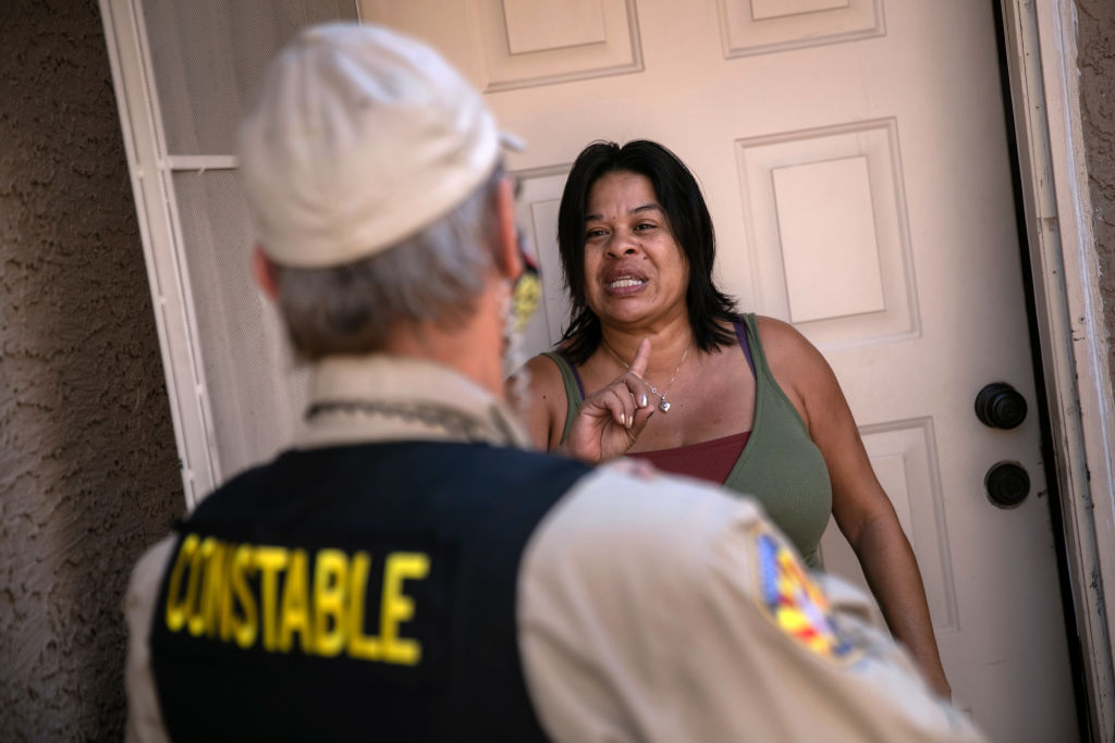 A tenant speaks with a Maricopa County constable who arrived with an eviction order on October 7, 2020 in Phoenix, Arizona.