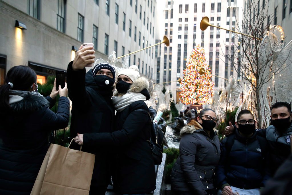 A couple wearing protective masks take a selfie with the Rockefeller Christmas Tree in the background on Dec. 6, 2020 in New York City.