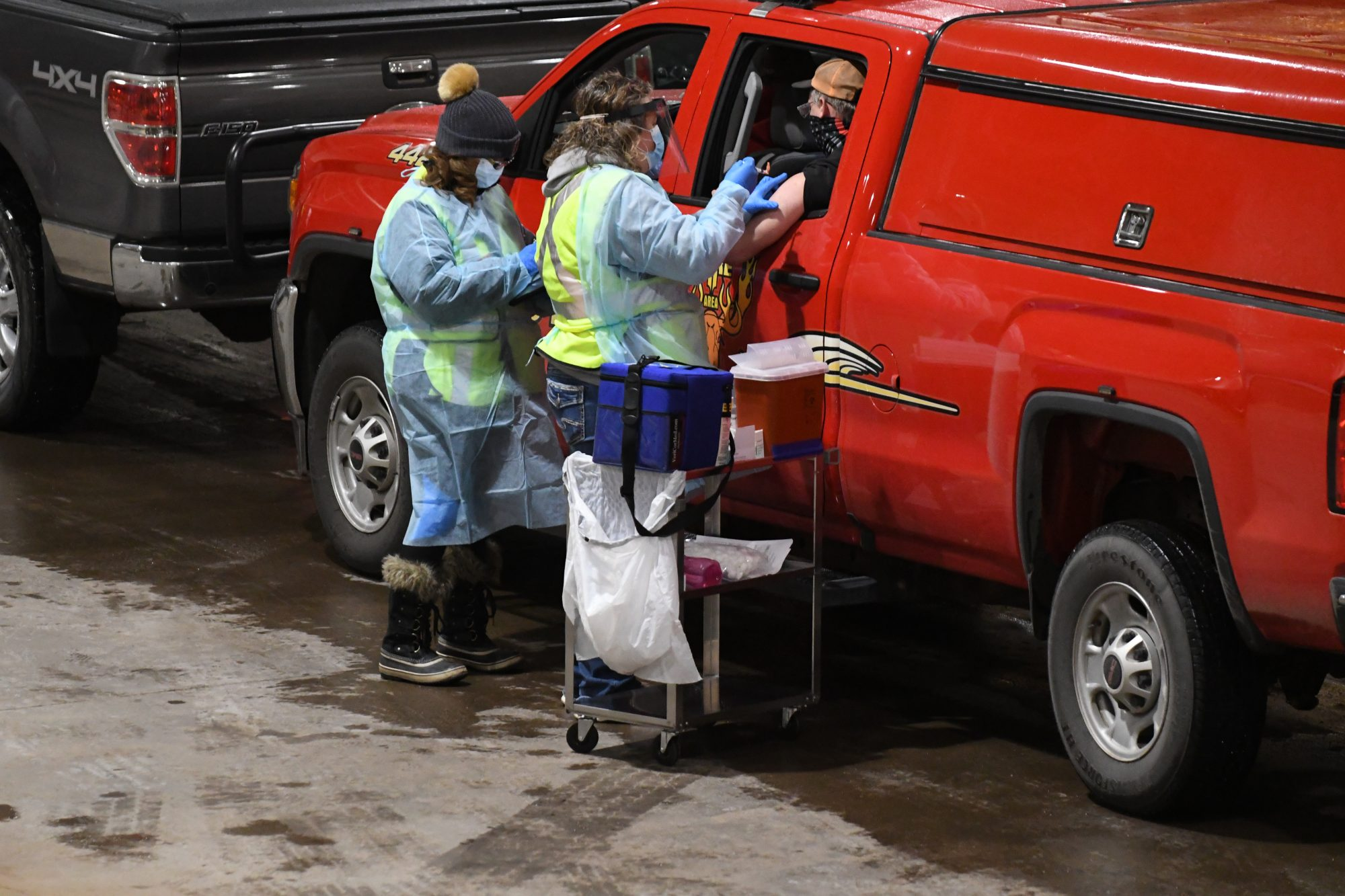 A fire fighter receives a COVID-19 vaccine shot on day one of Carlton County's drive-through vaccination clinic, on Dec. 29, 2020, in Carlton, Minn.