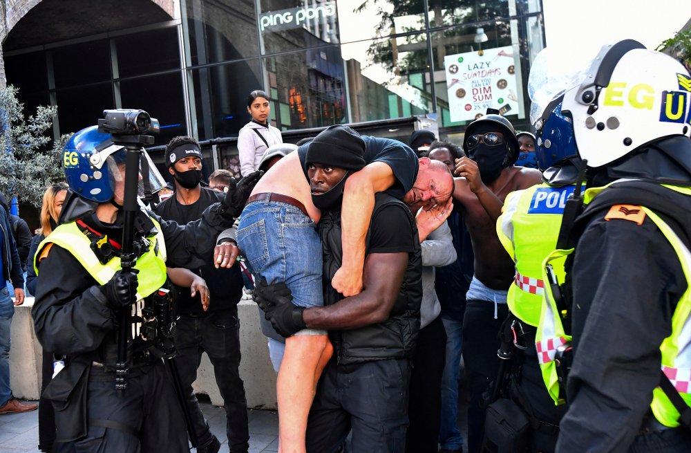During a Black Lives Matter demonstration in London on June 13, protester Patrick Hutchinson carries an injured counter-protester to safety near Waterloo Station.