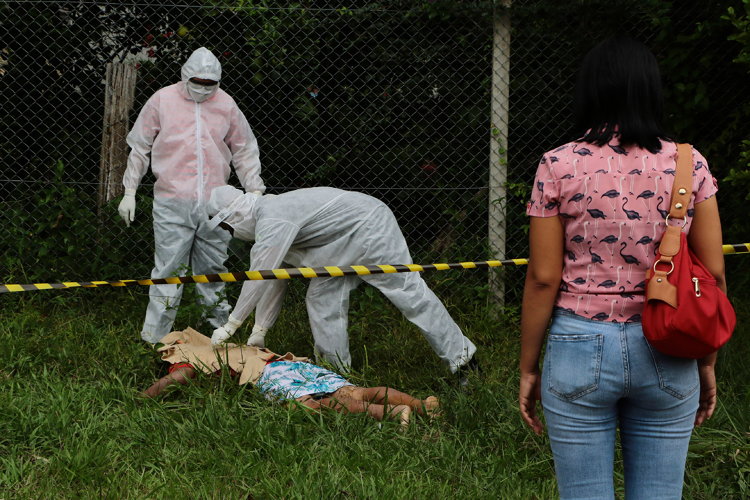 Government funeral workers cover the body of Arlen Laranjeira Bezerra, 39, near the Delphina Rinaldi Abdel Aziz Hospital in Manaus, in the Brazilian state of Amazonas, on May 5. Bezerra had been admitted to the hospital to undergo treatment for COVID-19. After escaping from the hospital at dawn, his body was found by family members approximately 650 feet (200 meters) away.