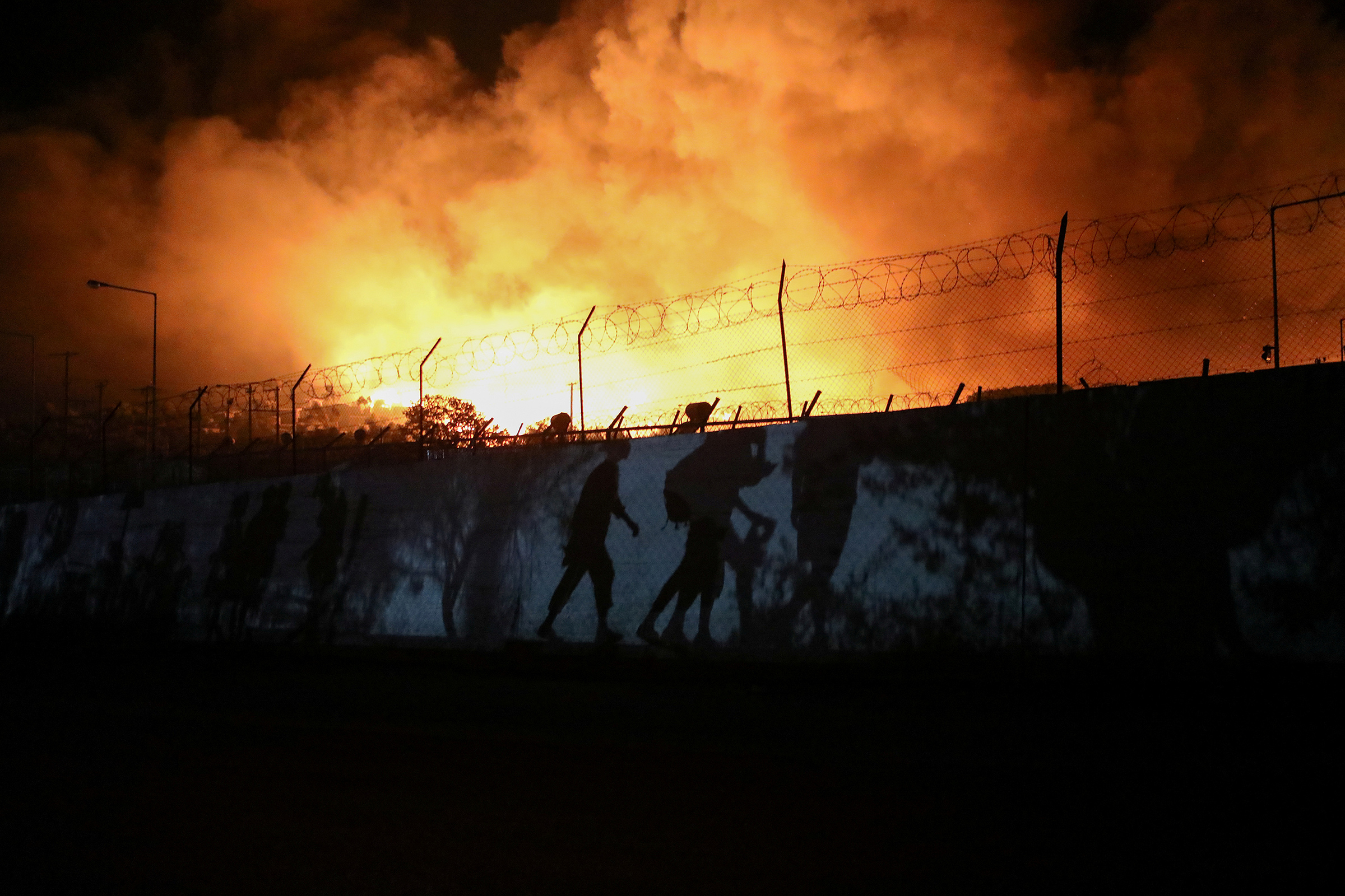 Shadows of refugees and migrants carrying their belongings are seen as they flee from a fire at the Moria camp on the Greek island of Lesbos on Sept. 9.