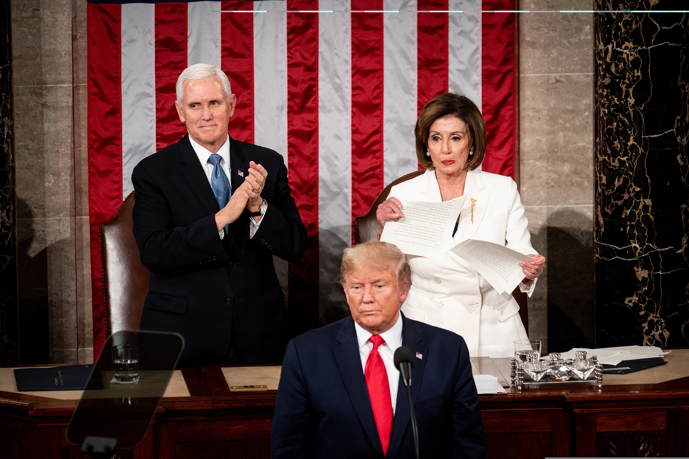 As Vice President Mike Pence applauds, House Speaker Nancy Pelosi rips up her copy of President Trump's State of the Union address following his speech at the Capitol in Washington, D.C., on Feb. 4.