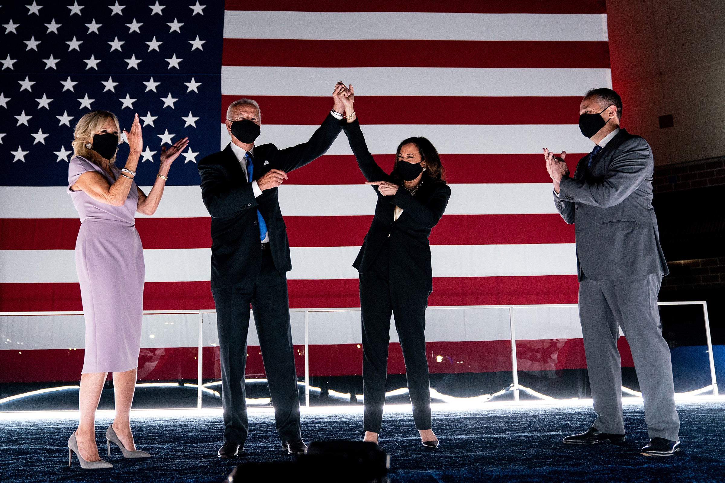 Former Vice President Joe Biden and Sen. Kamala Harris are applauded by their spouses, Jill Biden and Douglas Emhoff, shortly after Biden accepted his party's presidential nomination during the Democratic National Convention in Wilmington, Del., on Aug. 20.