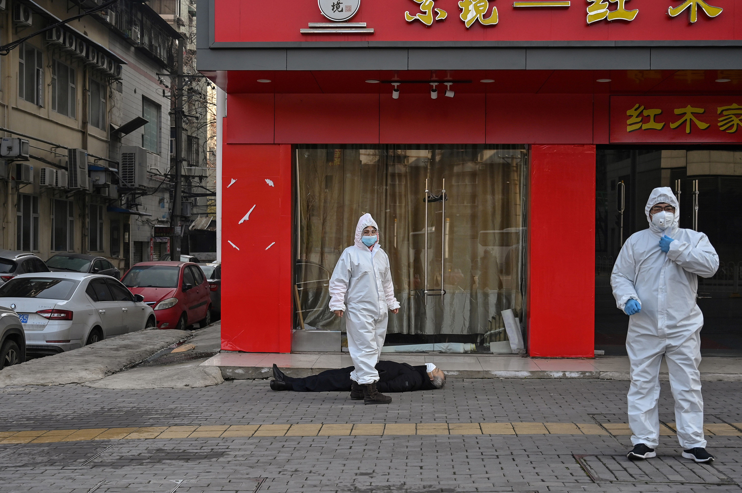Officials in protective suits near an elderly man who collapsed and died near a hospital in Wuhan, China, on Jan. 30.