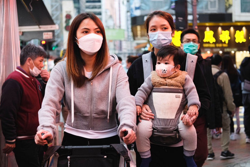 People wear protective mask and walk on the street on December 15, 2020 in Hong Kong, China.