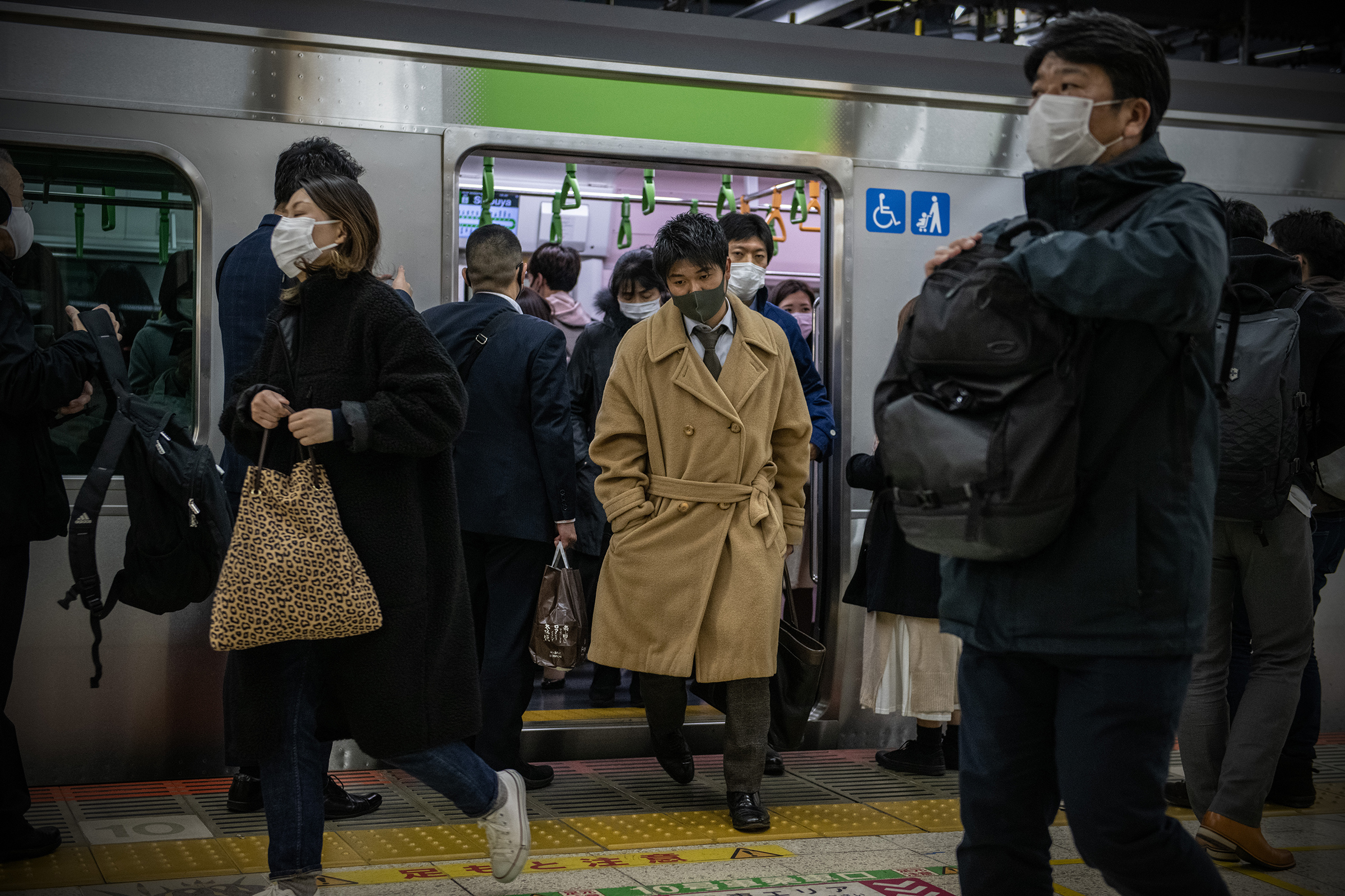 People wearing face masks disembark a Yamanote Line train on Dec. 16 in Tokyo