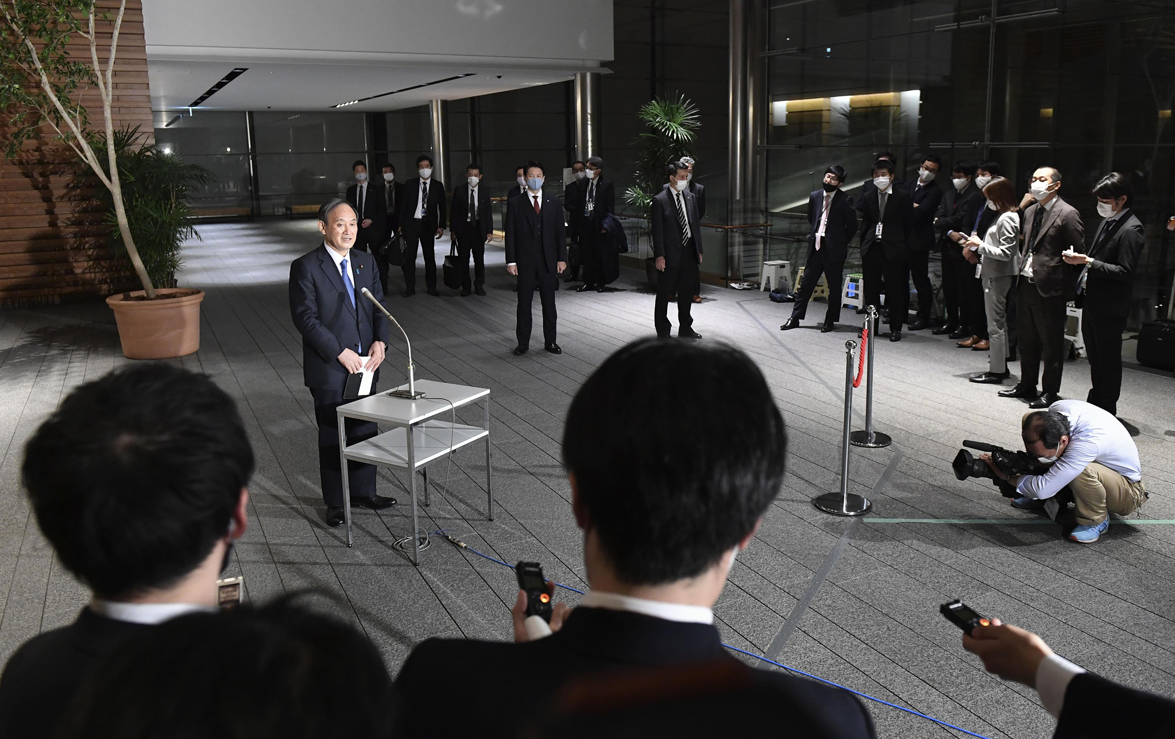 Japanese Prime Minister Yoshihide Suga speaks to reporters at his office in Tokyo on Dec. 14. The government's Go To Travel campaign will be halted from Dec. 28 to Jan. 11 amid a surge in coronavirus cases