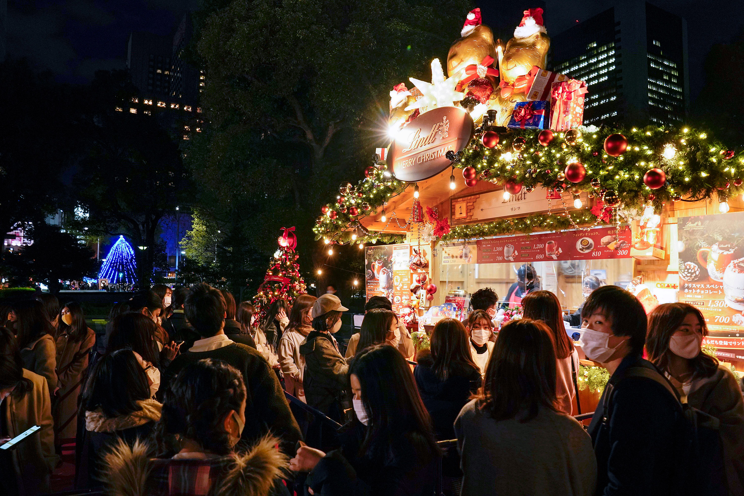 Visitors wearing protective masks enjoy their time at a Christmas market in Tokyo on Dec. 16 after Tokyo government announced it marked its highest record of 678 new COVID-19 infection cases in a day