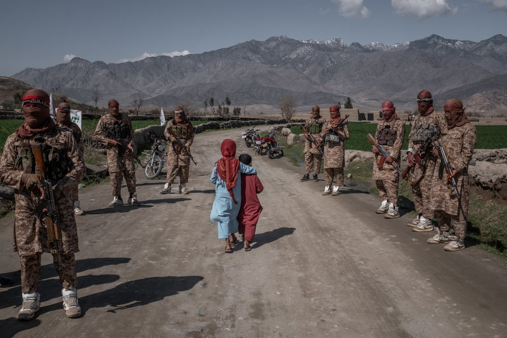 Two children pass members of a Taliban Red Unit, an elite force, in the Alingar District of Afghanistan's Laghman Province on March 13.