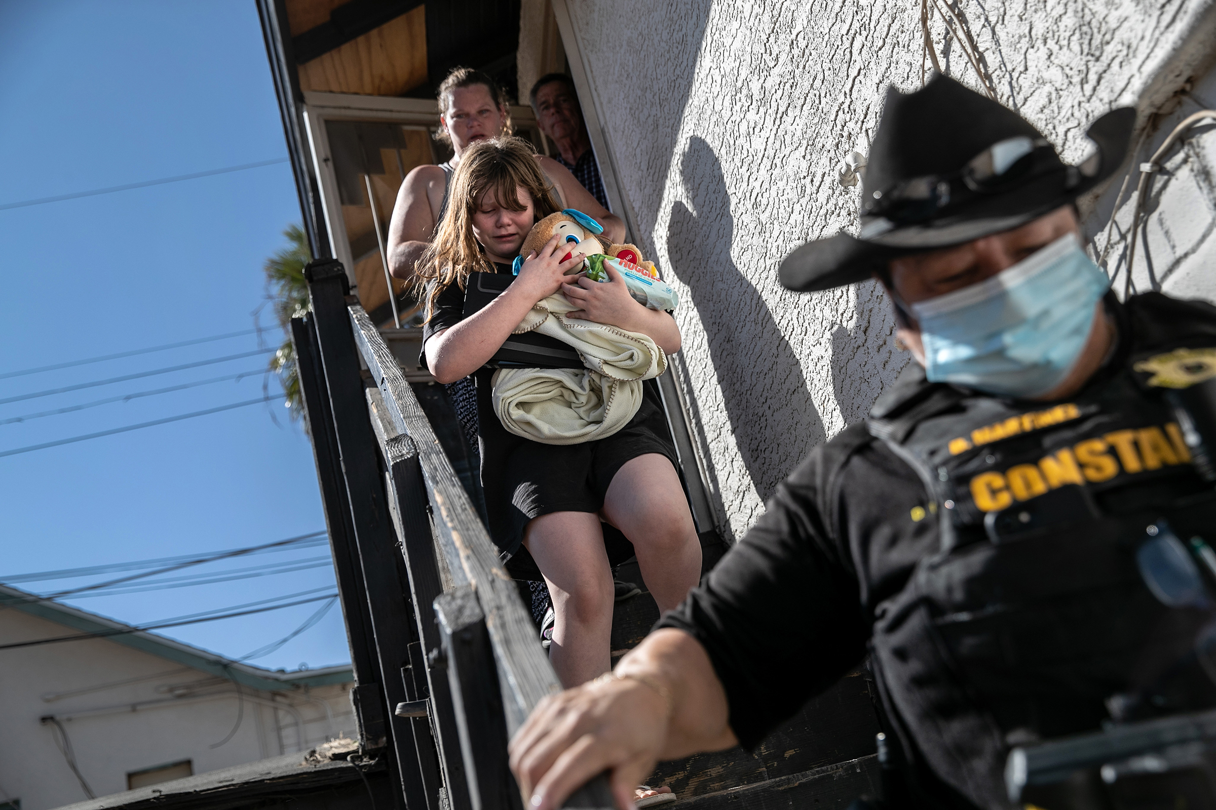 Maricopa County Constable Darlene Martinez escorts a family out of their apartment after serving an eviction order for non-payment in Phoenix, Ariz., on Sept. 30. Thousands of court-ordered evictions continued nationwide despite a CDC moratorium for renters impacted by the pandemic.