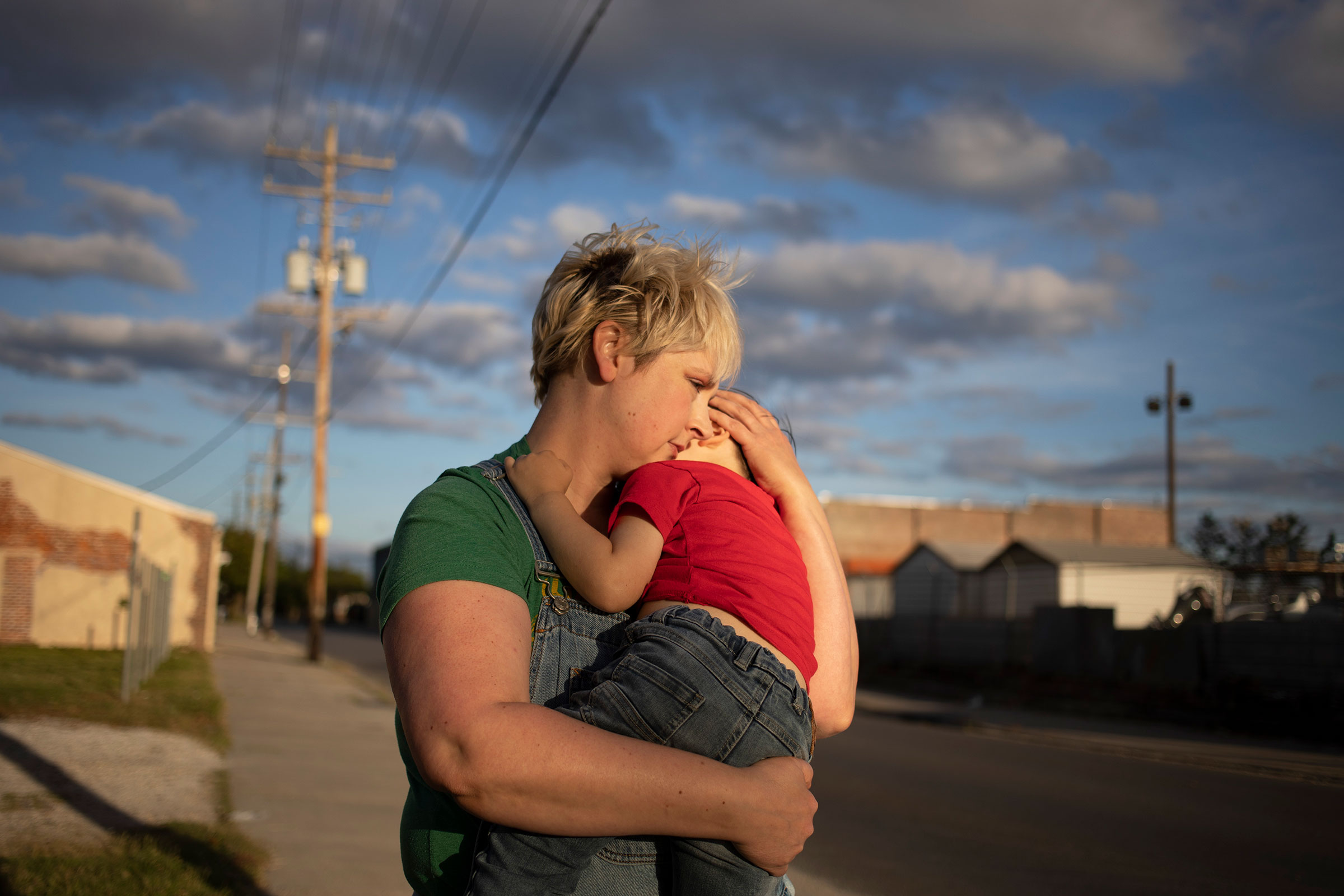 Laurie Halbrook, a registered nurse, holds her son Michael, 3, during a walk through their neighborhood in New Orleans.