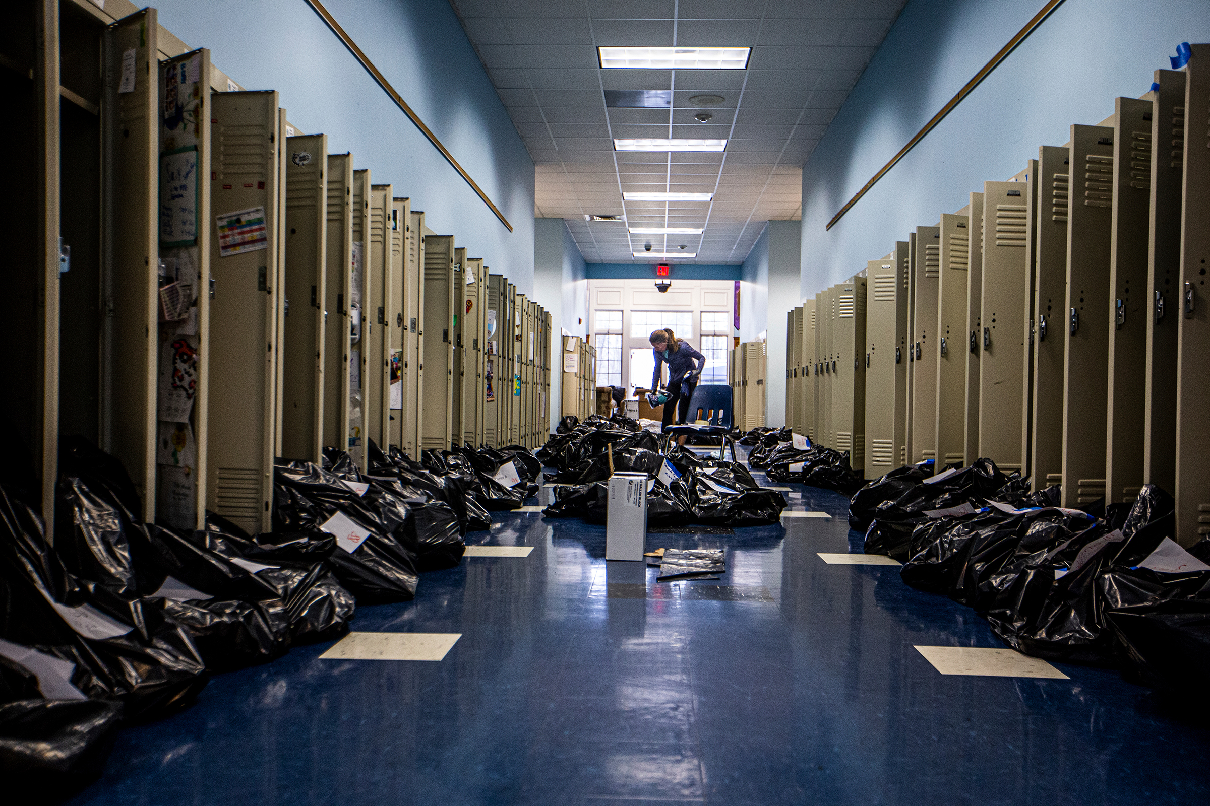 Kelen Walker packs students' locker contents into black trash bags as they clean and sanitize the school while students take online classes from home at Canterbury School in Greensboro, N.C., on March 17.