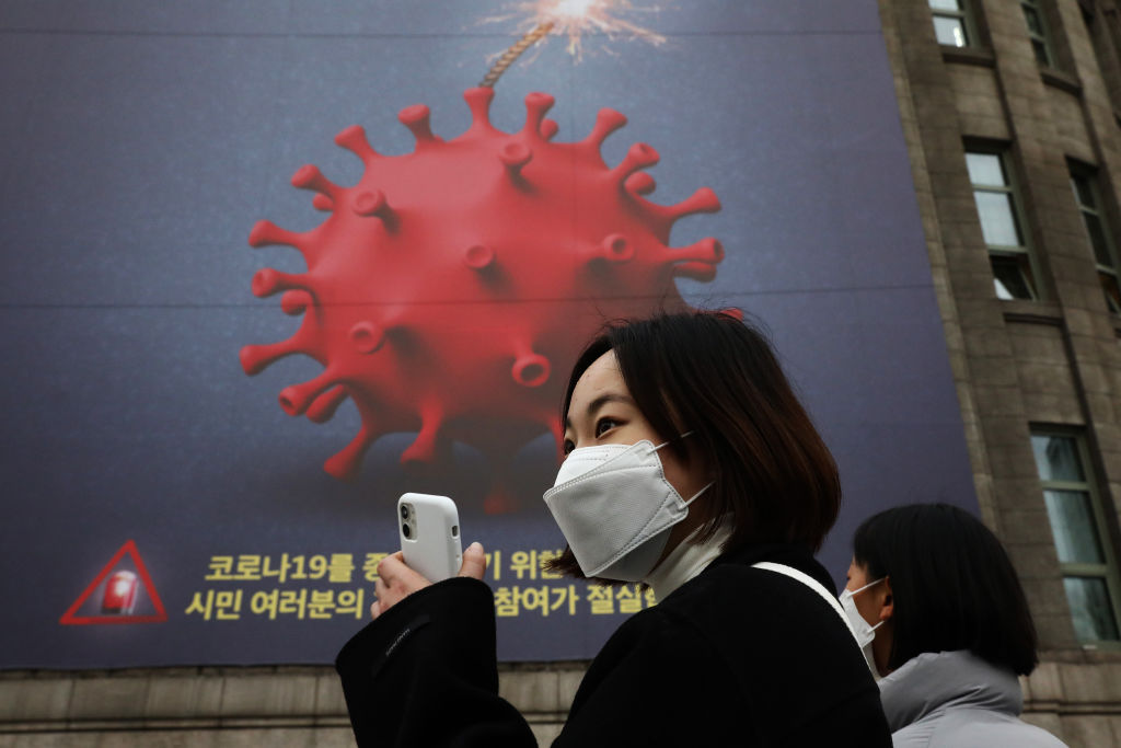 People wearing masks to prevent the spread of COVID-19 walk in front of a banner emphasizing an enhanced social distancing campaign displayed on the wall of Seoul City Hall on November 25, 2020 in Seoul, South Korea. Authorities announced the tightening of social distancing regulations and the closure of some kinds of businesses, including nightclubs, to combat a quickly increase wave of Covid-19 infections this week.