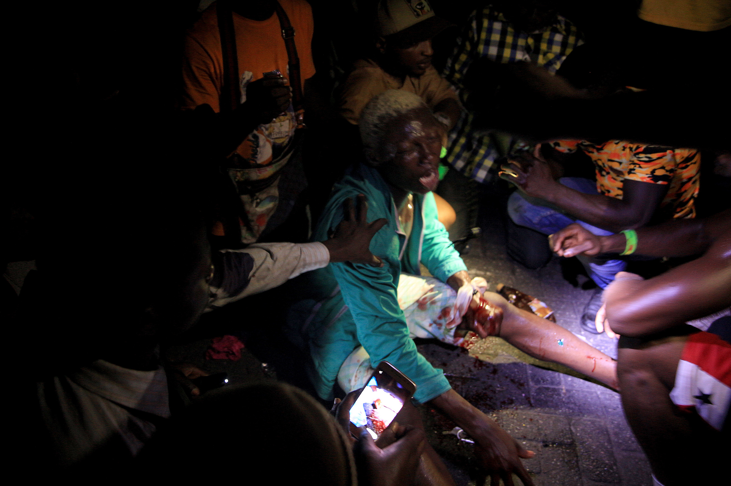People come to the aid of a man who was wounded when security forces officers opened fire on a protest against brutality at the Lekki toll gate on Oct. 20, 2020.