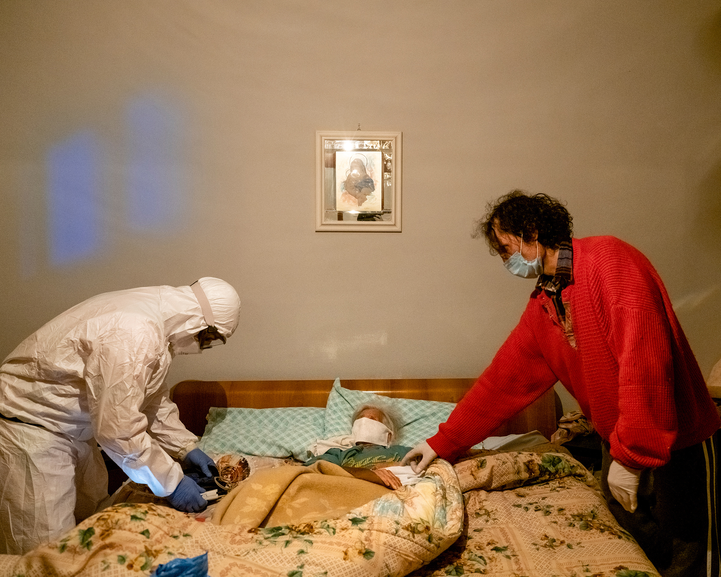 A health worker checks an elderly woman's oxygen level, after receiving a call about a suspected COVID-19 case, in the northern Italian province of Bergamo.