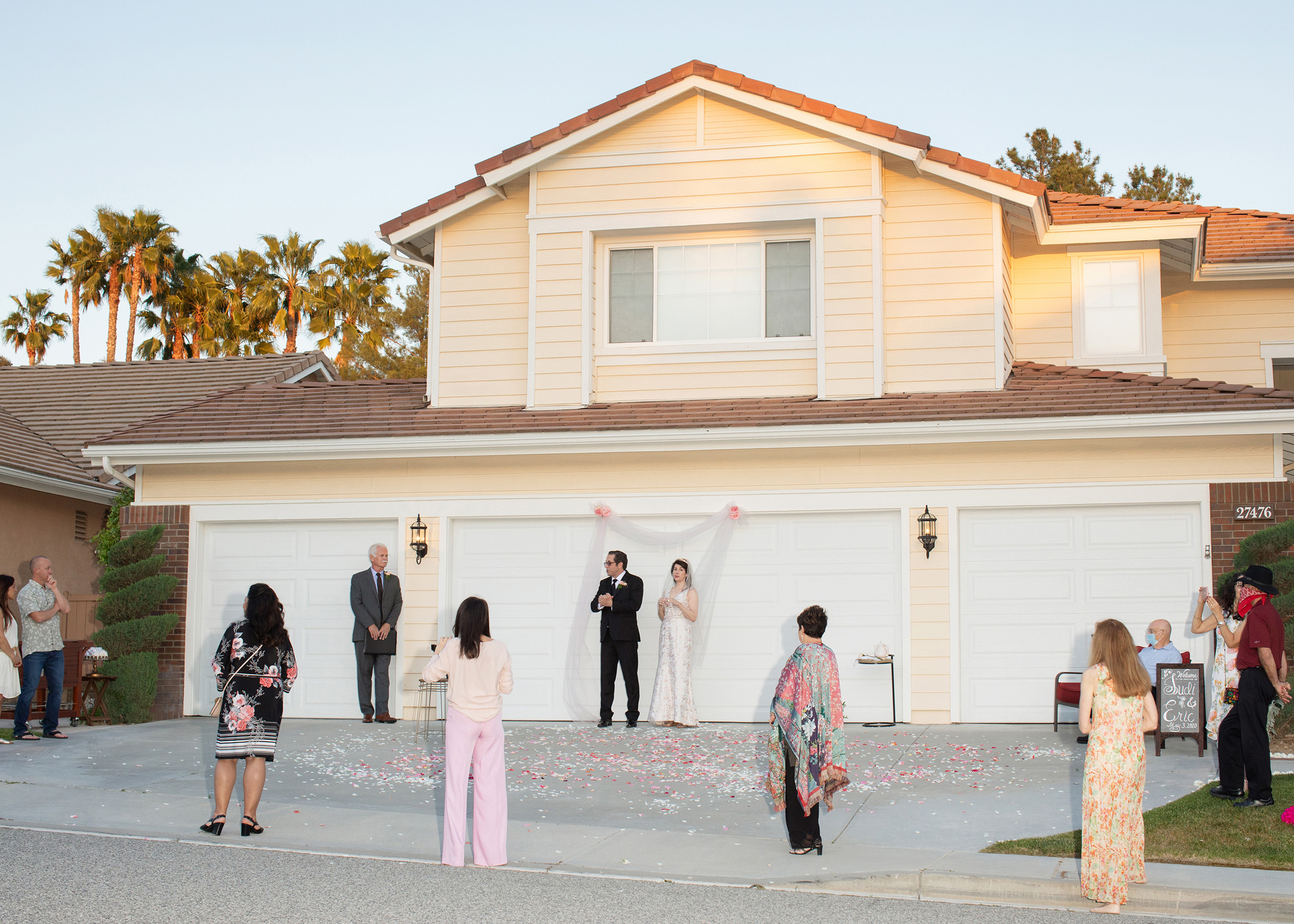 After pushing their wedding date back a few times due to pandemic concerns, Judi and Eric finally decided to move forward with an intimate wedding in front of their home in Santa Clarita, Calif., in May. Judi's main concern was that her elderly father, who is undergoing treatment, might not make it to their new date in 2021 and it was extremely important to her that he was there to walk her down the aisle. Everything fell into place perfectly, the photographer recalled. Their wedding officiant, who lived across the street, and a few neighbors and close friends joined for the small ceremony in their driveway.