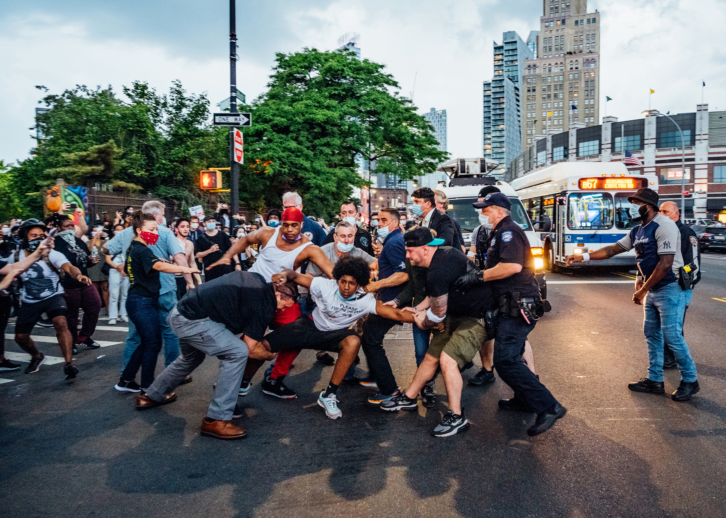 A protester, wearing a shirt that reads  Please Stop the Violence,  is dragged near Brooklyn's Barclays Center on May 29, four days after George Floyd's killing.