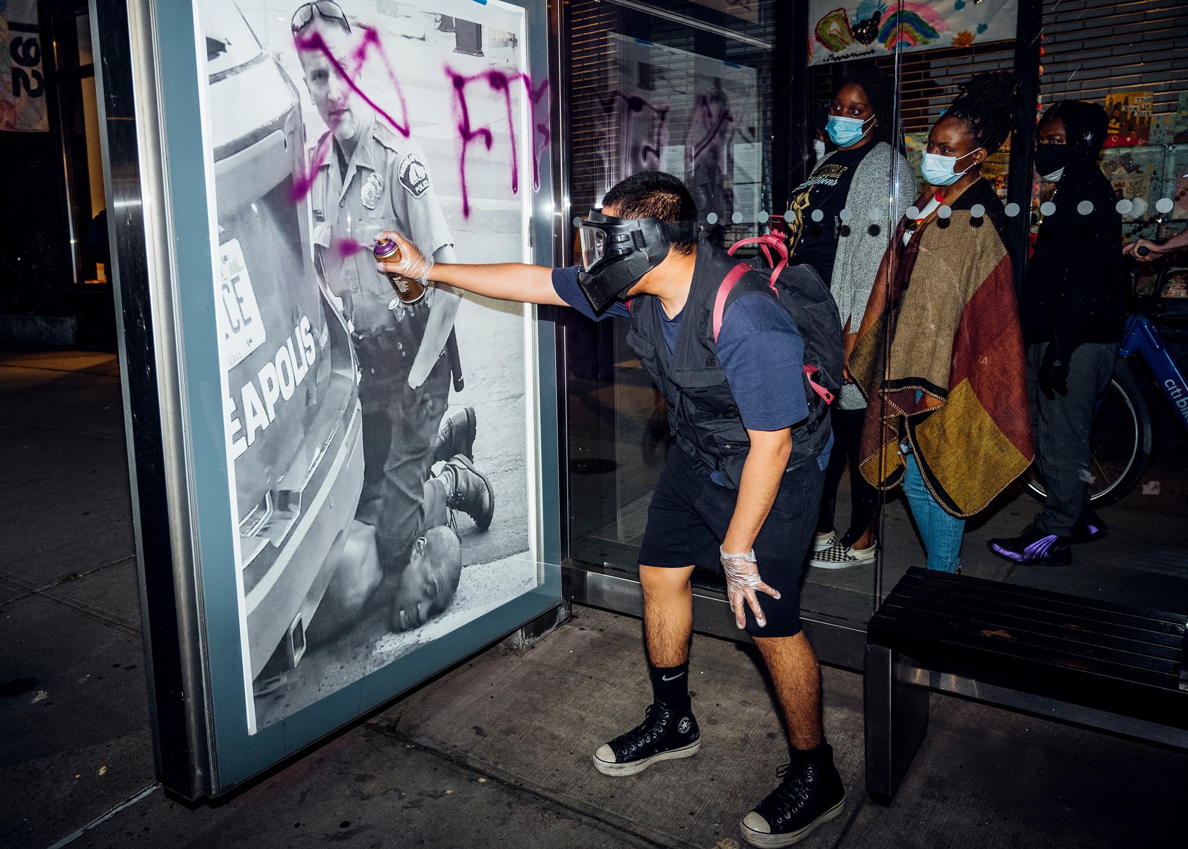 "On May 31, a demonstrator in New York spray-paints a poster of Derek Chauvin's knee on George Floyd's neck. ""Out of nowhere, this guy pulled out a purple spray can and just started writing on it,  the photographer recalled.  These ladies were walking by and paused to look at it. They were looking at it, like, 'Is this to attack us or to stop us from being silent?'"""
