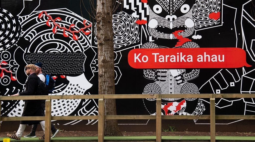 People walk past Maori language signs in Wellington, New Zealand, on Sept. 13, 2018.