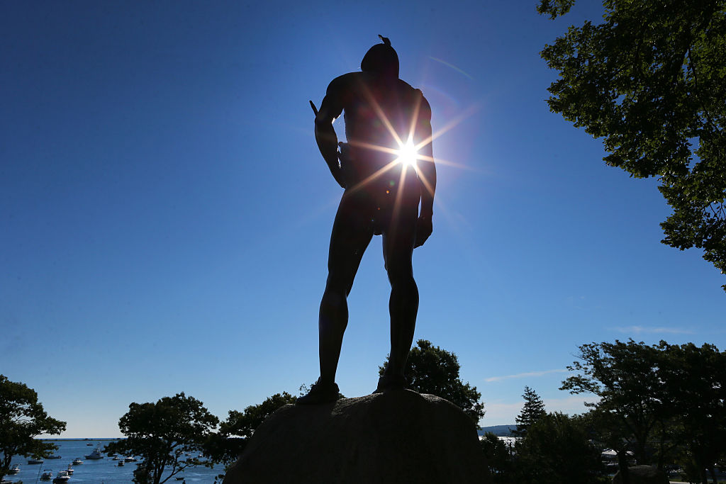 Sun shines through the statue of Wampanoag Indian chief Massasoit that stands atop a hill overlooking Plymouth Rock in Plymouth, Mass., on Aug. 27, 2015.