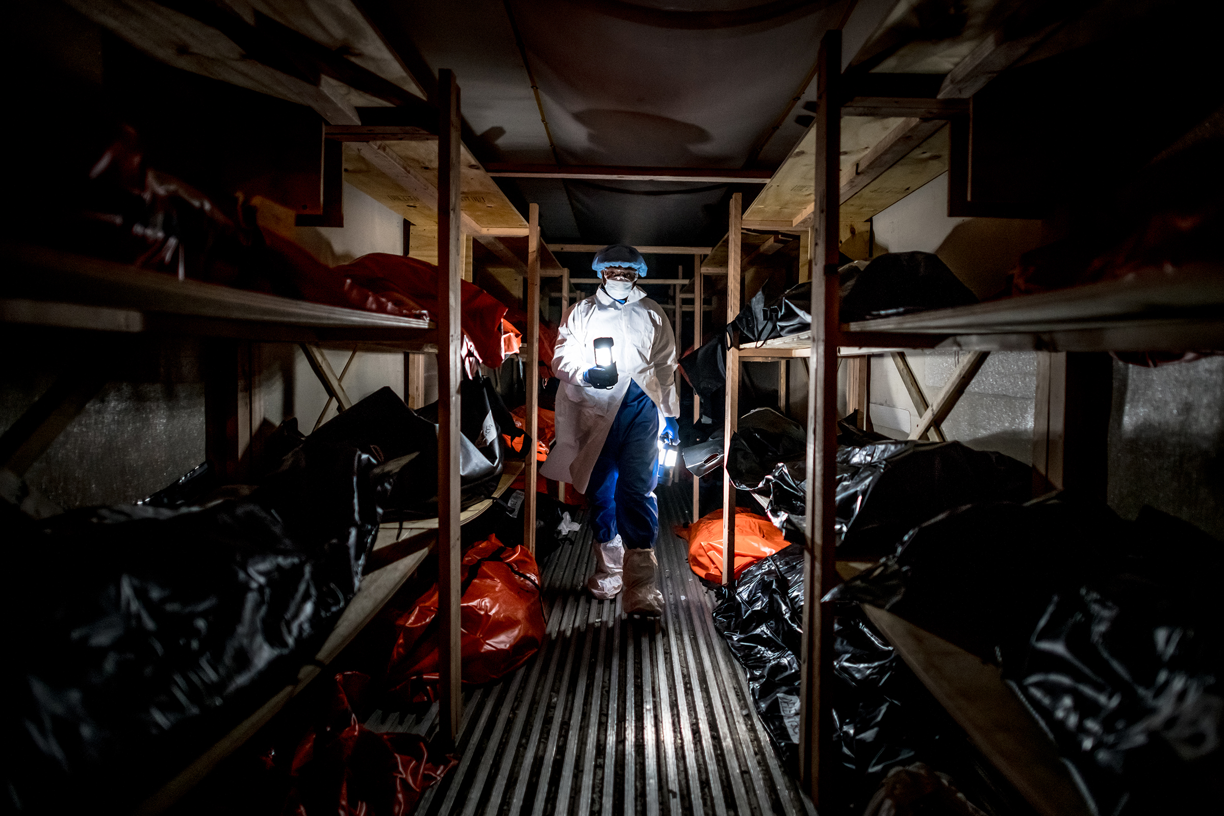 "Kyle Edwards, 39, collects lanterns from inside a temporary morgue outside the Wyckoff Heights Medical Center on April 22. Edwards, whose job sometimes involved moving bodies of COVID-19 victims to the morgue, worked 7 a.m. to 10 p.m. shifts during the worst of the pandemic and, like many members of his team, contracted the virus. His family asked him to take time off until the virus died down, but Edwards kept working. He and his wife trained their 5-year-old son to not hug him immediately when he gets home: ""Daddy has to wash the coronavirus off him when he gets home from the hospital,"" the boy will tell others."