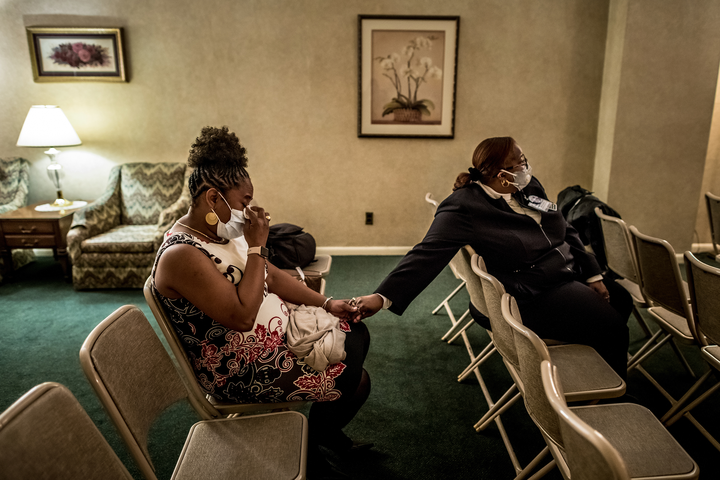 Marsha Williams, left, patient-care coordinator at Wyckoff's women's health center, wipes away tears and holds the hand of co-worker Erica Davis during union delegate Jacqueline Venner's funeral. (Because of social-distancing restrictions, capacity was limited to 10 people.) Williams, whom Venner helped navigate her job, said she respected her like  a big sister.