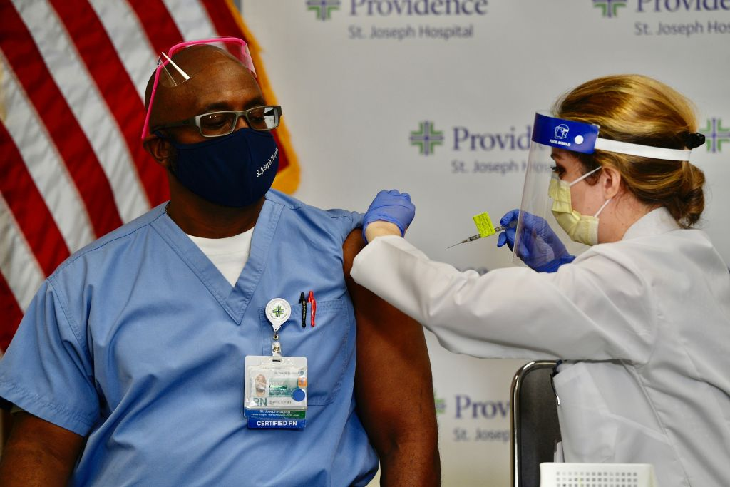 Nurse Michael Lowman gets his first dose of the Pfizer-BioNTech COVID-19 vaccine from nurse practitioner Christie Aiello at Providence St. Joseph Hospital in Orange, CA, on Dec. 16, 2020.