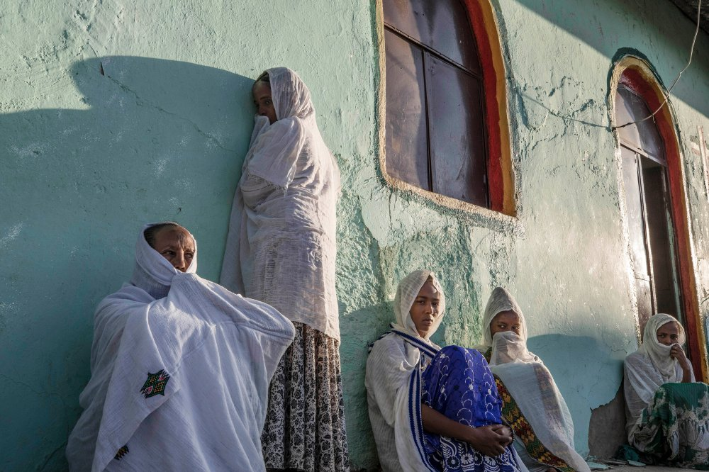 Women who fled the conflict in Ethiopia's Tigray region pray during Sunday Mass at a church near Umm Rakouba refugee camp in Qadarif, eastern Sudan, on Nov. 29.