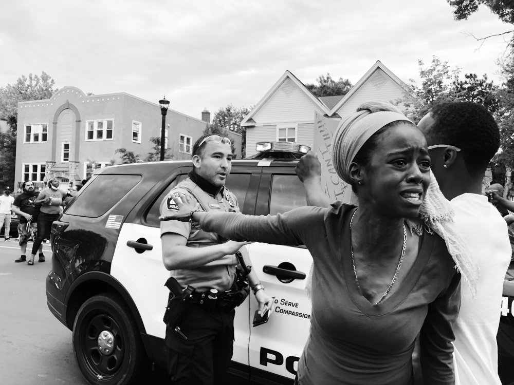 A woman outraged by the killing of George Floyd speaks to a crowd and blocks a police officer's vehicle with a group of protesters in Minneapolis on May 27.