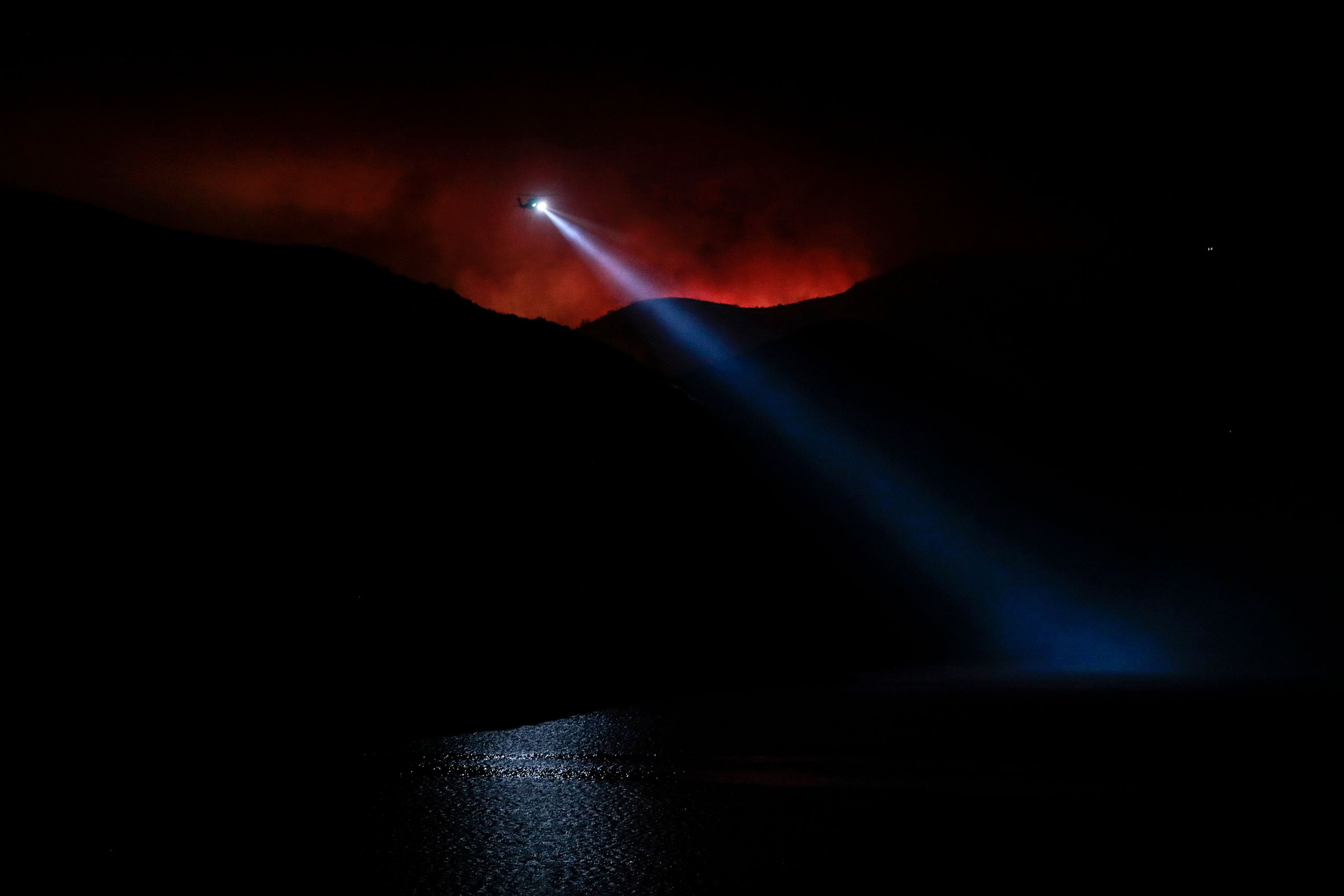 The night sky glows red from the Holser Fire in Piru, Calif., on Aug. 17, as a water-dropping helicopter works to slow the spread of flames.