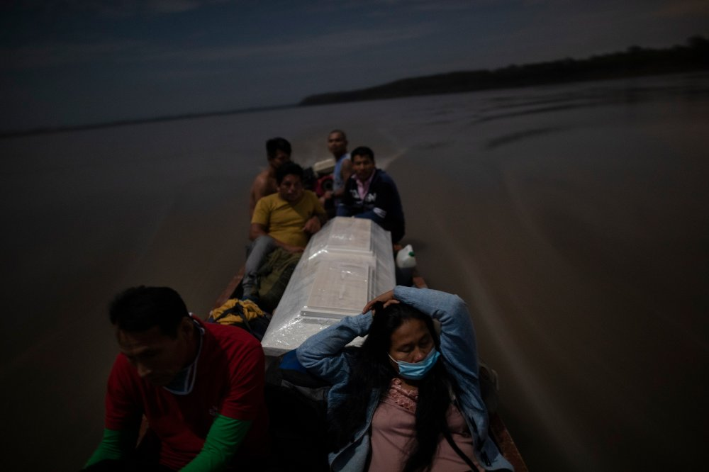 Relatives accompany the coffin of Jose Barbaran, who was believed to have died from coronavirus complications, as they travel by boat on Peru's Ucayali River on Sept. 29. Despite the risk, family members decided to travel by night to Barbaran's hometown of Palestina, a four-hour journey.