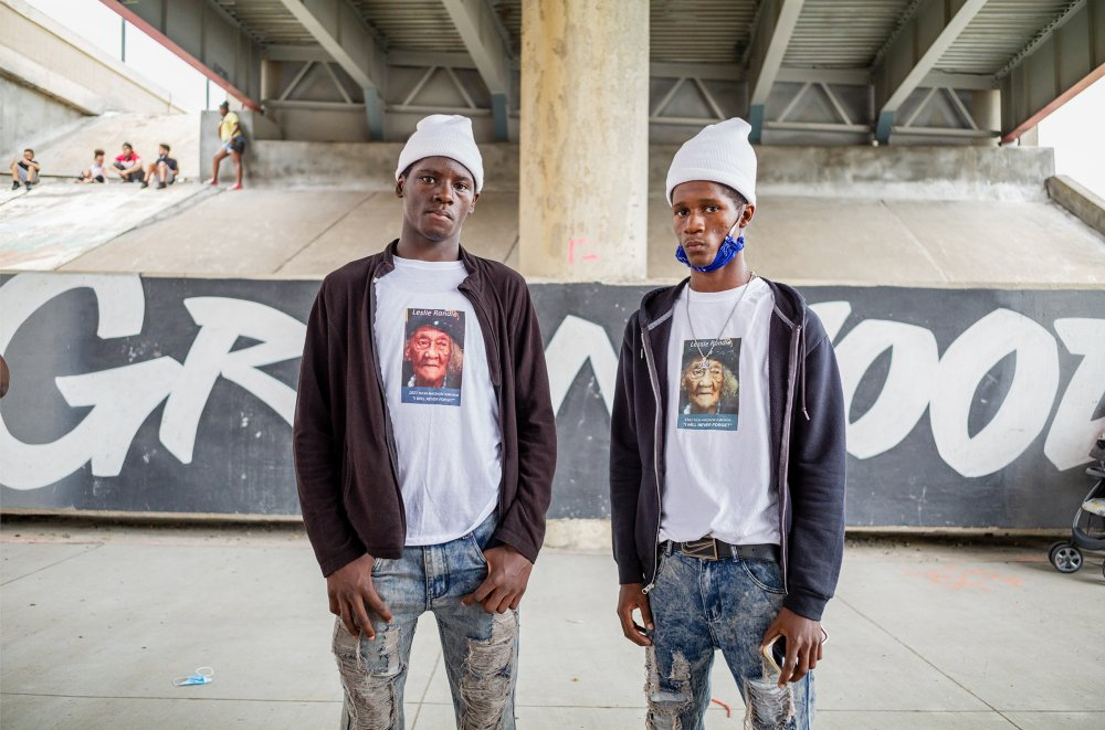 At Juneteenth celebrations in Tulsa's Greenwood district, the site of one of American history's worst-ever episodes of racial violence, Deshon and Omarion wear T-shirts depicting their grandmother Leslie Randle—who was alive during the 1921 massacre, when hundreds of Black-owned homes and businesses in the area were burned and more than 300 Black people were killed. She told us that the bodies were taken away and stacked on a hill up by [Oklahoma State University], says Deshon. Every time we heard the stories it made us upset. But she made us listen.