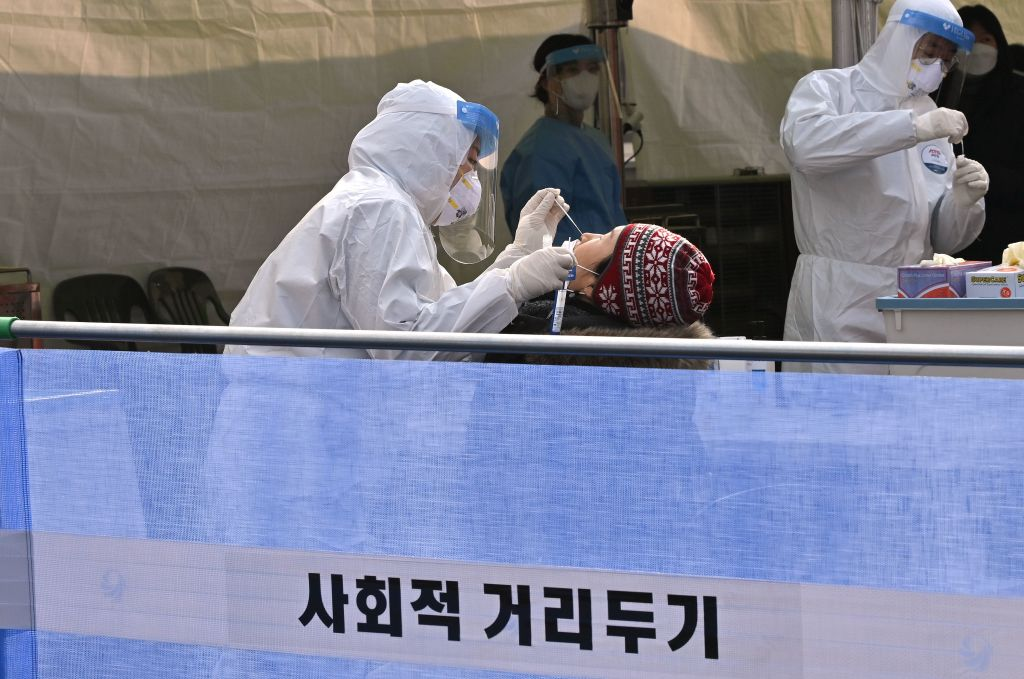 A medical staff member wearing protective gear takes a swab from a visitor to test for the Covid-19 coronavirus at a temporary testing station outside Seoul railway station in Seoul on December 22, 2020. (Photo by Jung Yeon-je / AFP) (Photo by JUNG YEON-JE/AFP via Getty Images)