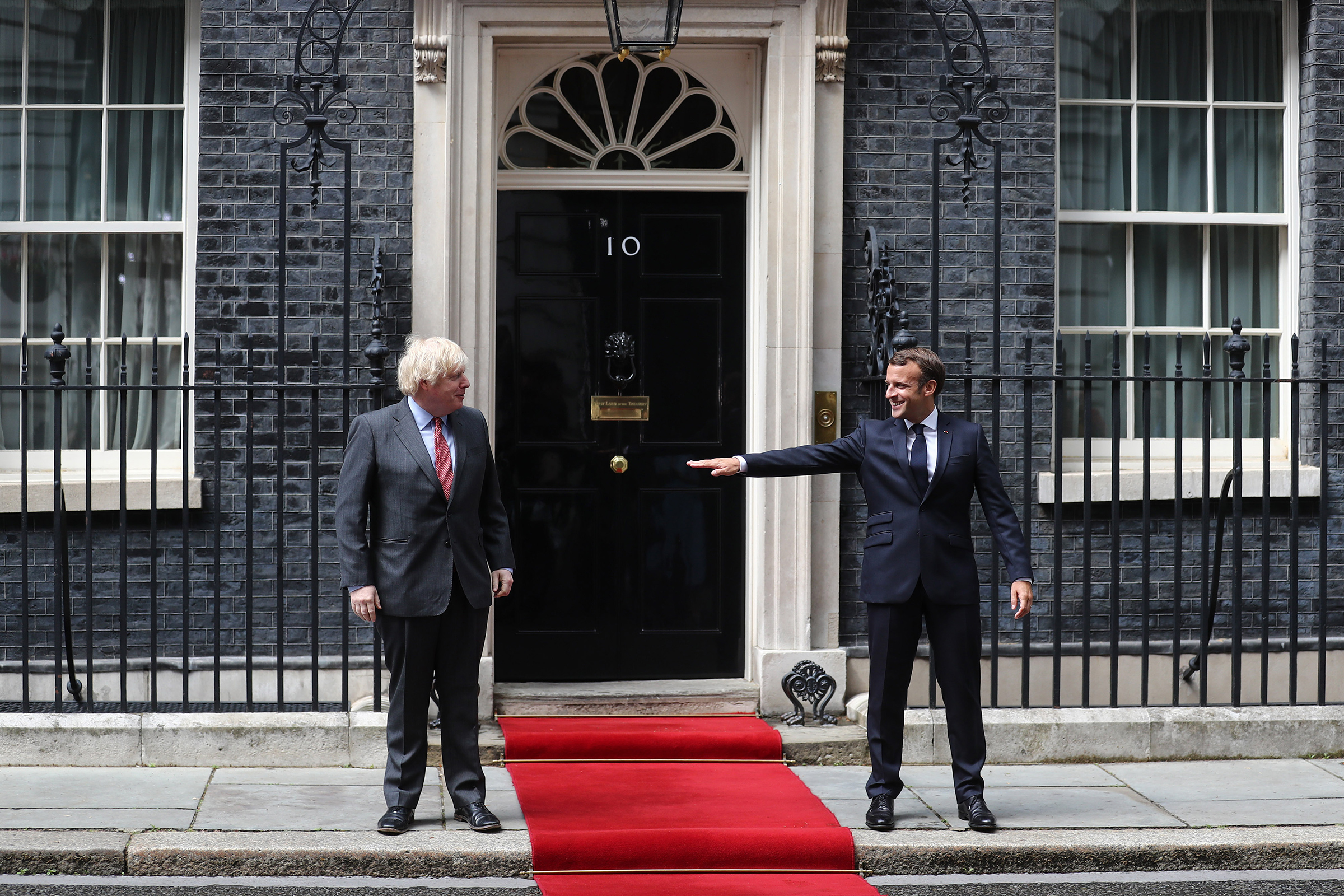 Boris Johnson, prime minister of the United Kingdom, and French President Emmanuel Macron stand socially distanced while posing for photographs at 10 Downing Street in London on June 18.
