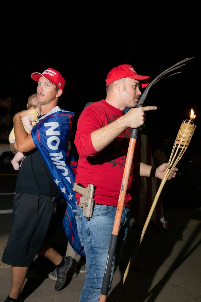 A man holding a child walks by a man with a rake, gun and tiki torch at the Maricopa County election office in Phoenix, Ariz., on Nov. 5.