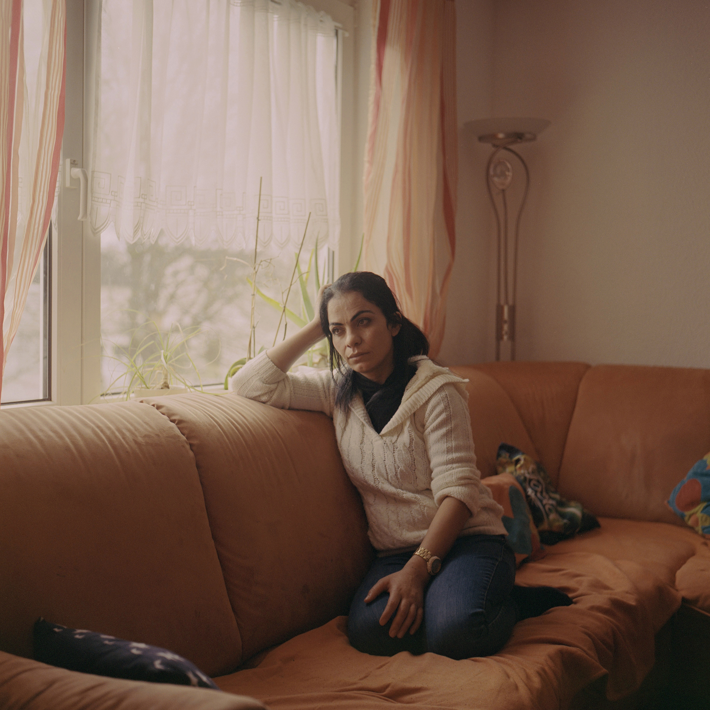 Hanan on the sofa in her living room in Germany.  A Radical German Program Promised a Fresh Start to Yazidi Survivors of ISIS Captivity. But Some Women Are Still Longing for Help,  Aug. 24.