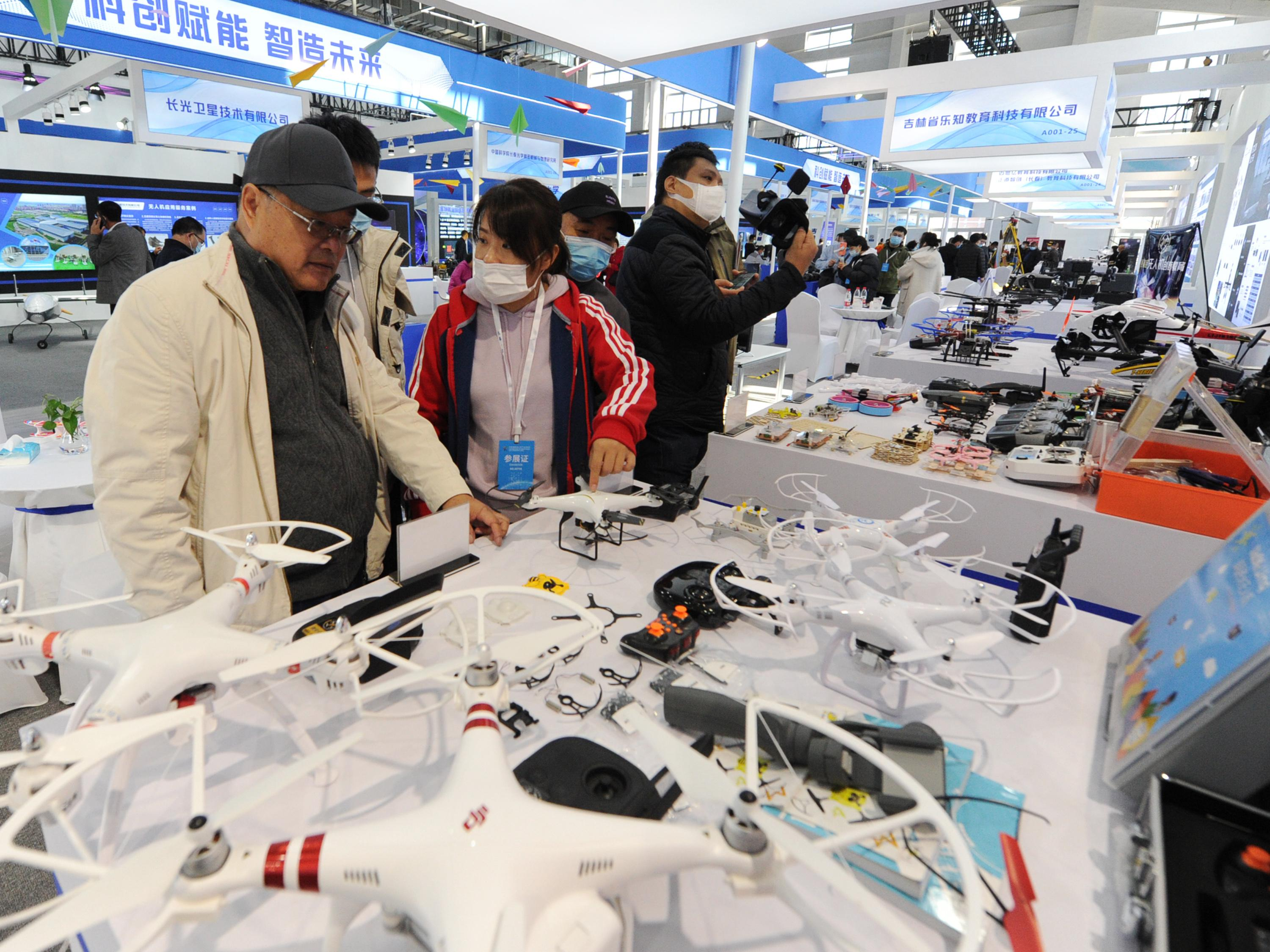 People look at drones at the DJI stand during the 2020 Changchun International UAV Industry Expo at CCIAFF Expo park on October 16, 2020 in Changchun, Jilin Province of China.
