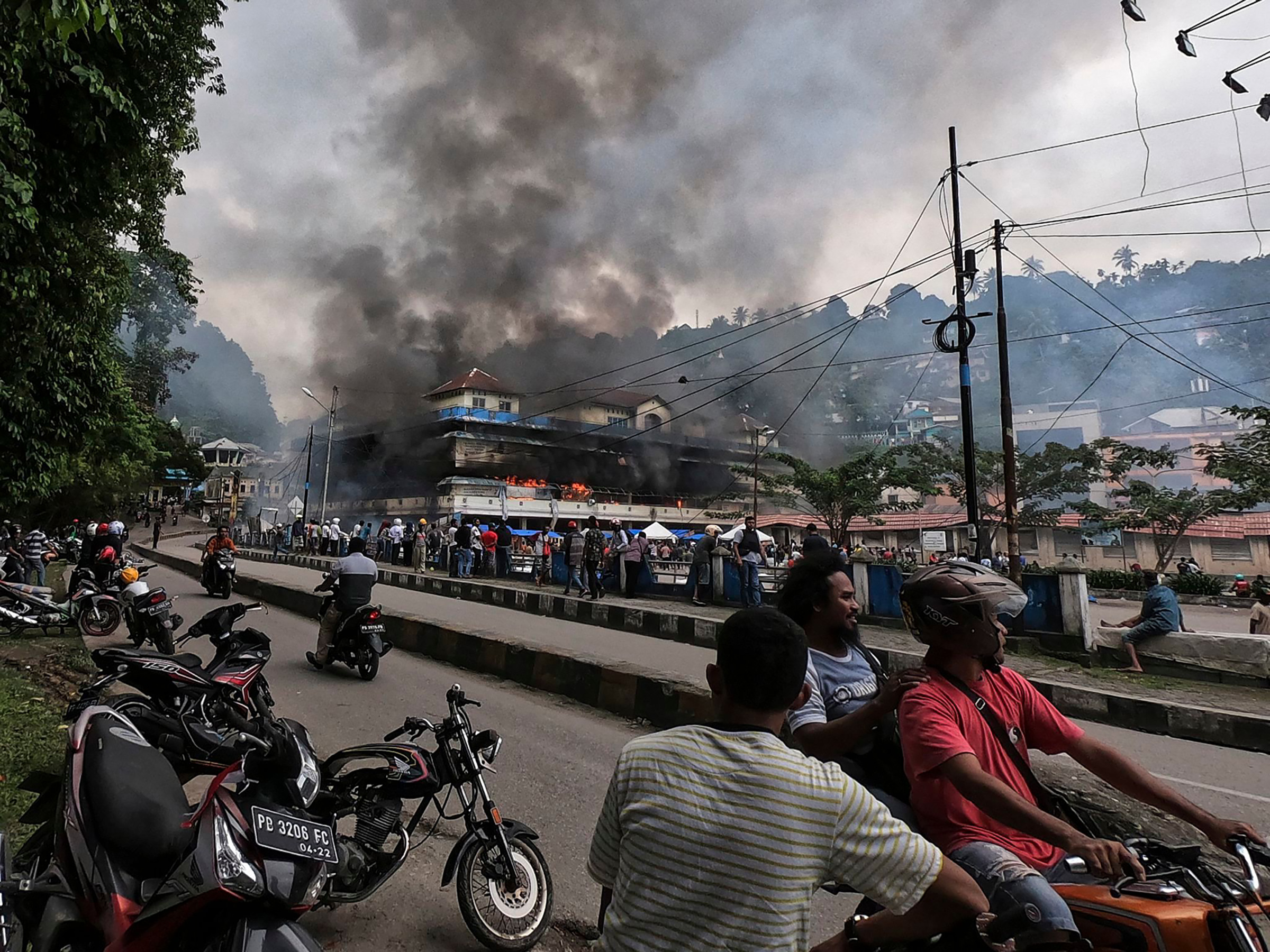 Papuans gather outside the burning Buruni market in Fakfak, West Papua, after it was torched by protesters on Aug. 2019 as unrest triggered by accusations that security insulted Papuan students in Surabaya continued