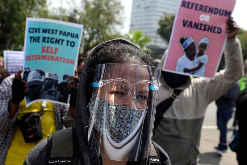 A Papuan pro-independence supporter wears a face shield during a rally commemorating the 58th anniversary of the New York Agreement outside the U.S. Embassy in Jakarta on Aug. 15. The agreement, signed by the Netherlands and Indonesia in 1962, led to Indonesia taking over West Papua from Dutch colonial rule in 1963