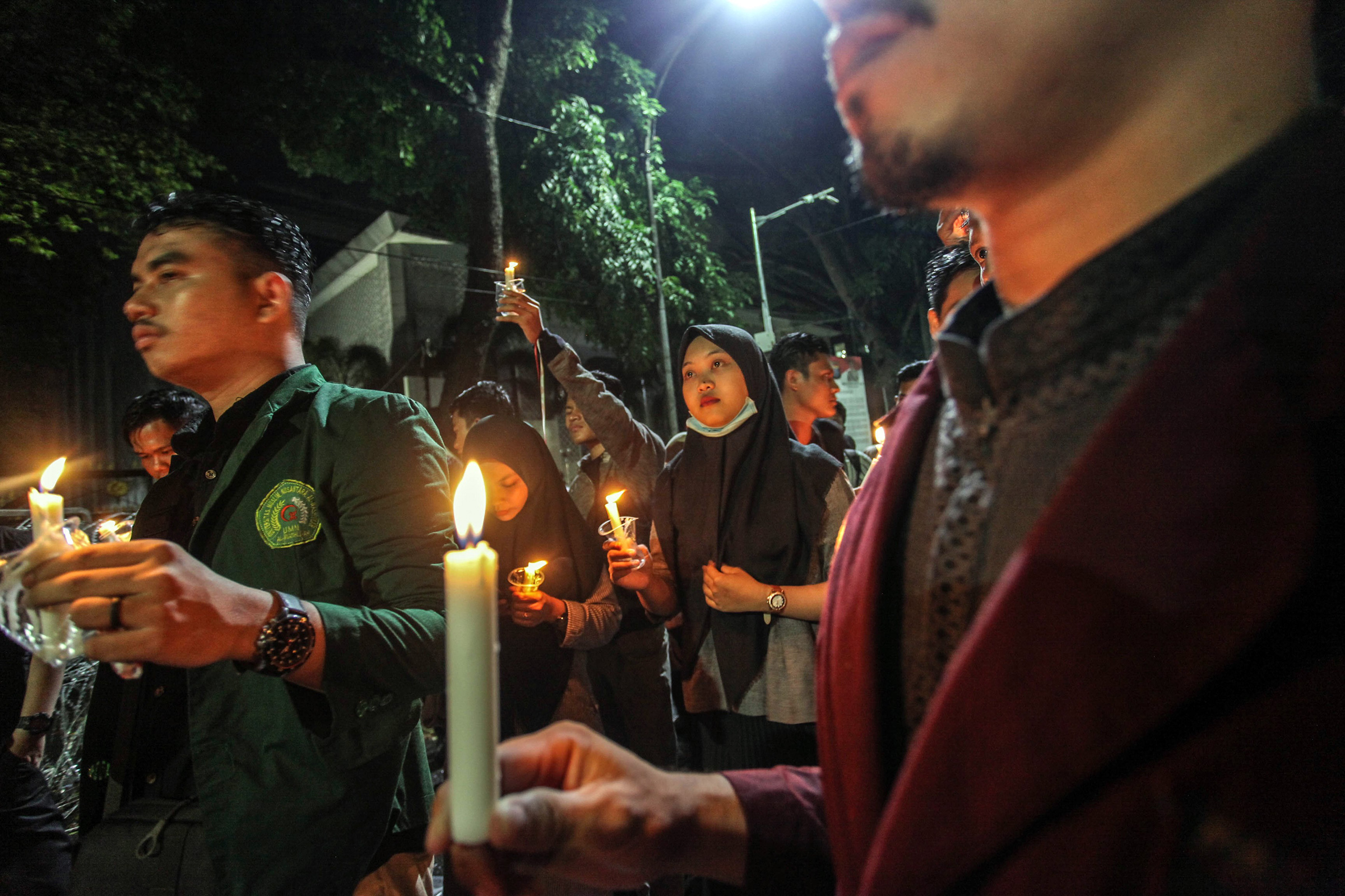 Indonesian students hold candles during a protest in Medan, Indonesia on Oct. 1, 2019 against the government's proposed change in its criminal code laws, plans to weaken the anti-corruption commission and riot victims in Wamena
