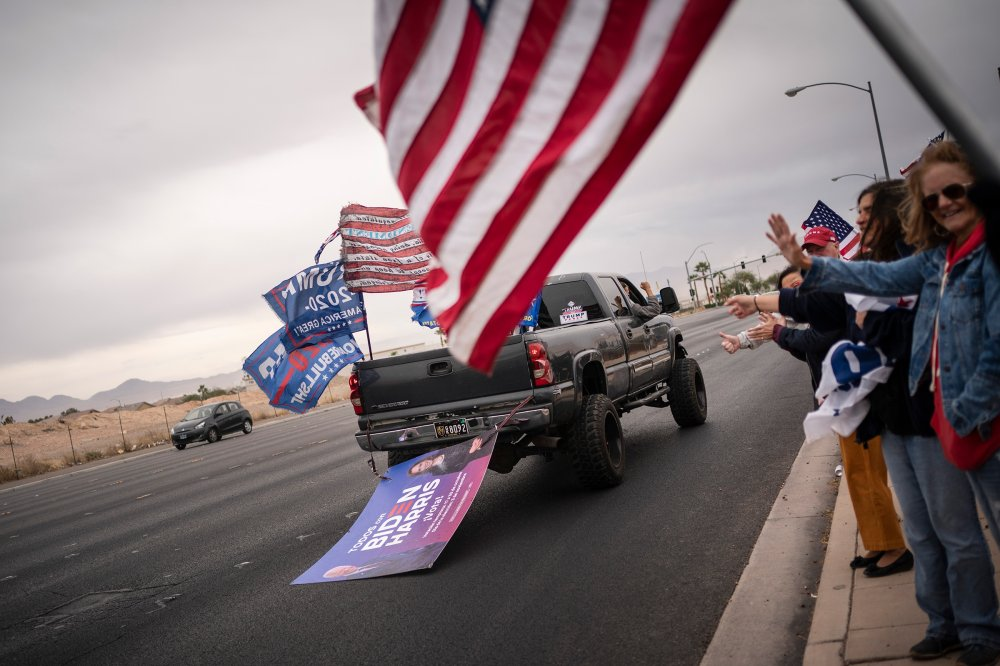 Supporters of President Trump wave at a pickup truck dragging a sign supporting Joe Biden and Kamala Harris outside of the Clark County Elections Department in North Las Vegas on Nov. 7.