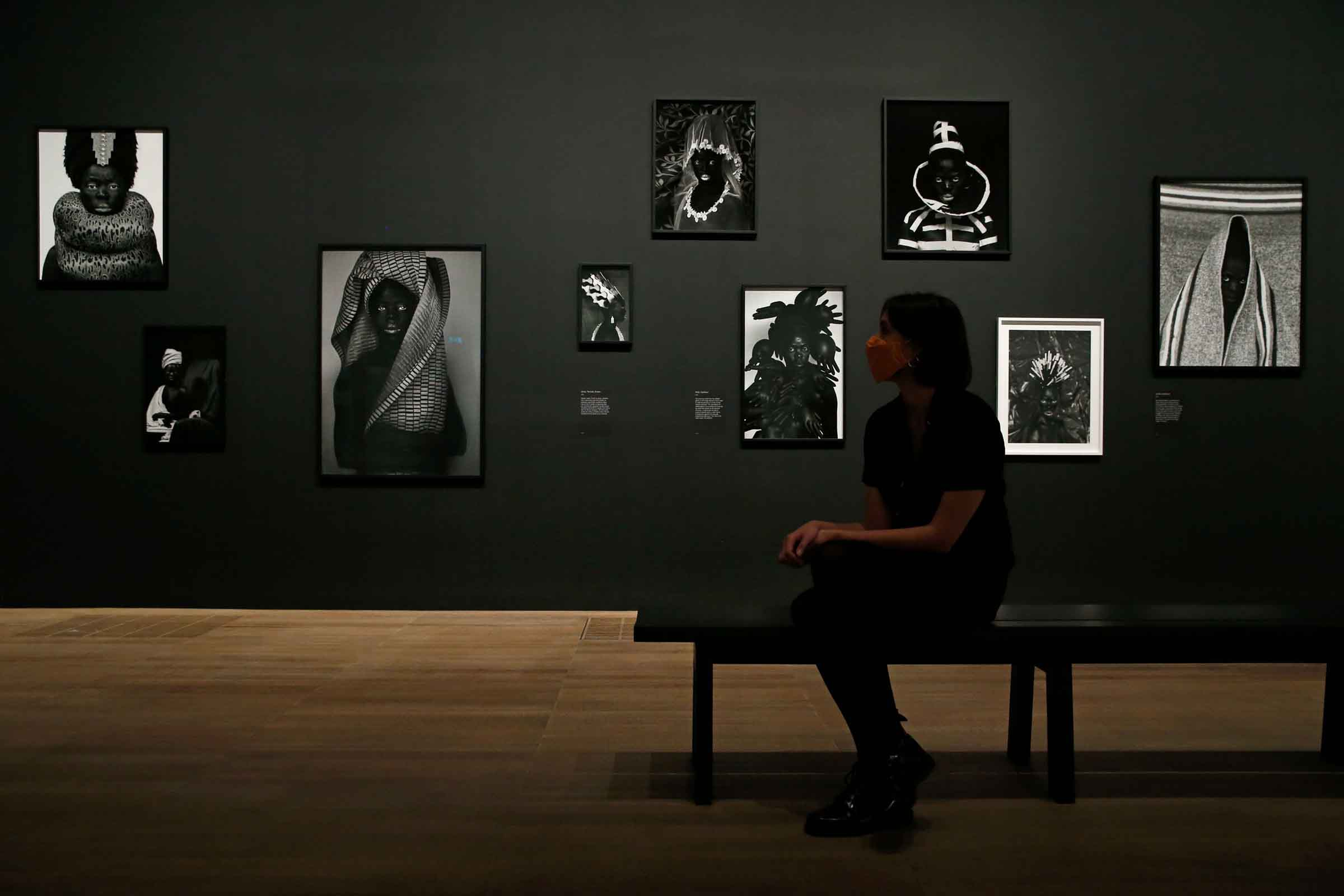 A Tate visitor poses in front of self portrait photographs from an on-going series entitled 'Somnyama Ngonyama' by South African visual activist Zanele Muholi in London on Nov. 3, 2020.