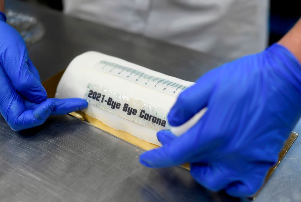 Bakery owner Tim Kortuem decorates a cake in the shape of a vaccination syringe and with the slogan '2021 Bye Bye Corona' at Schuerener Backparadies bakery in Dortmund, western Germany, during a partial lockdown to curb the spread of the ongoing novel coronavirus (Covid-19) pandemic. - Germany on January 5, 2021 prolonged and toughened its partial lockdown until January 31. (Photo by Ina FASSBENDER / AFP) (Photo by INA FASSBENDER/AFP via Getty Images)