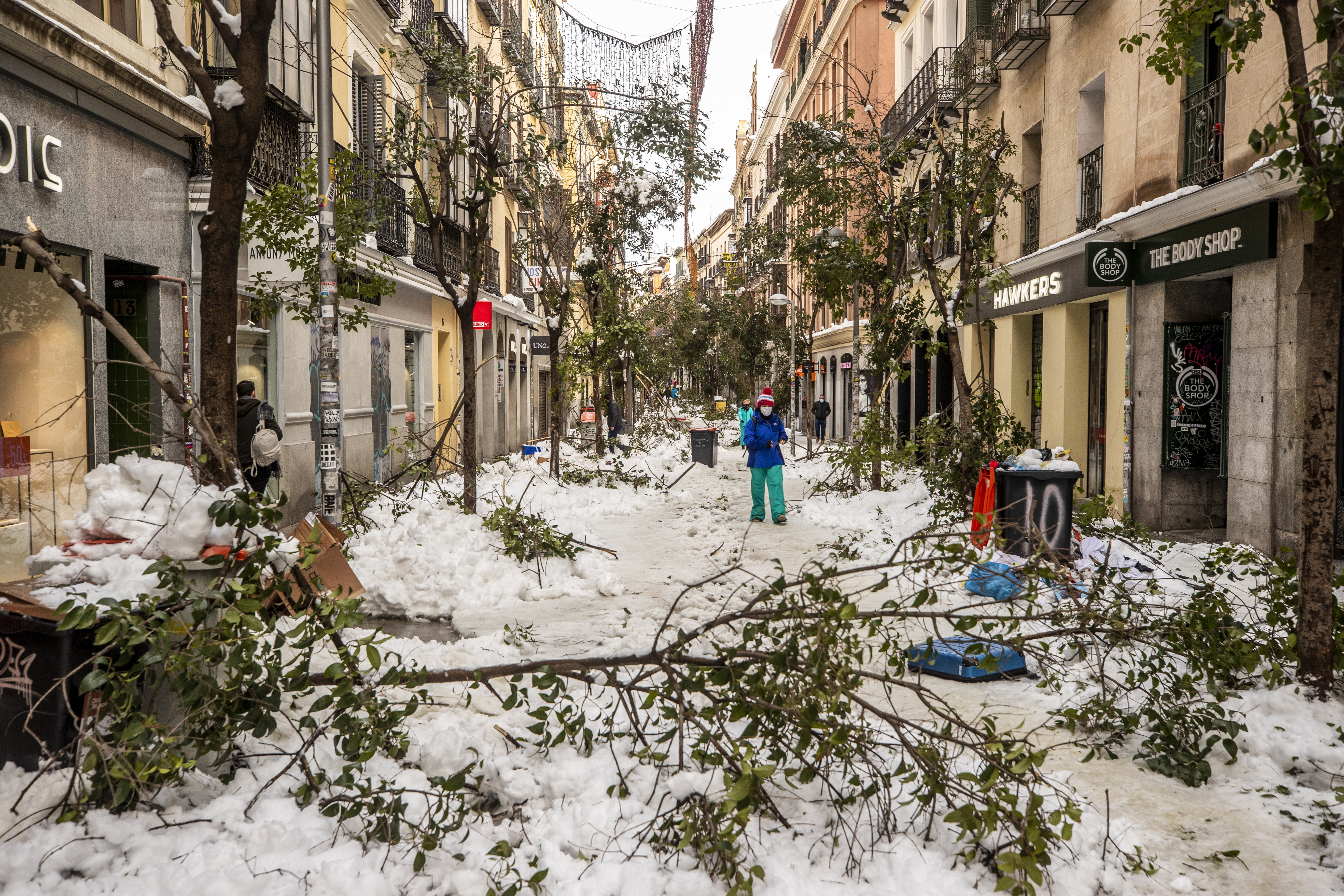 People walk along a street with snow and fallen tree branches during after a heavy snowfall in downtown Madrid, Spain, on Jan. 10, 2021.
