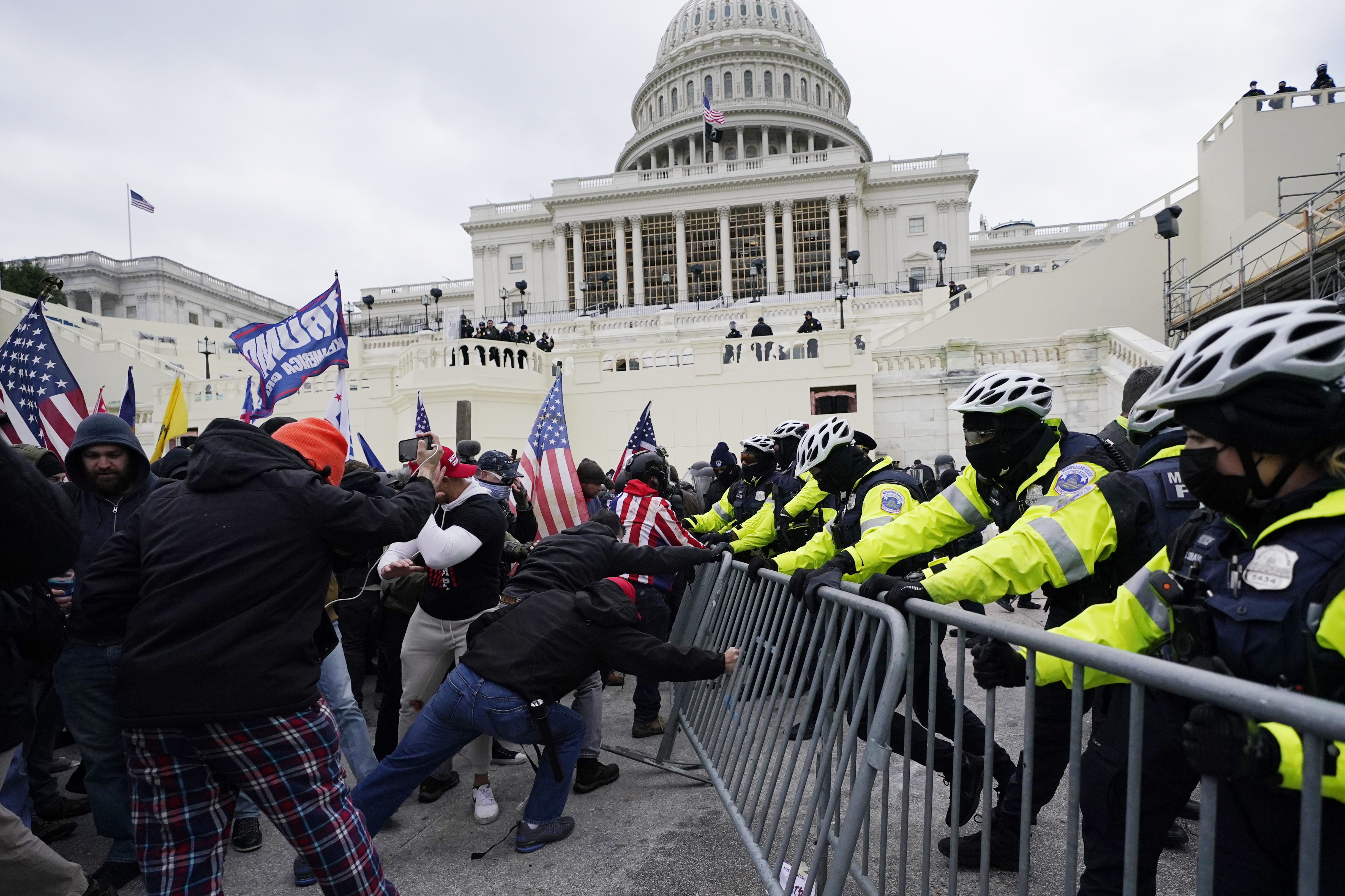 In this Wednesday, Jan. 6, 2021 file photo, Trump supporters try to break through a police barrier at the Capitol in Washington.