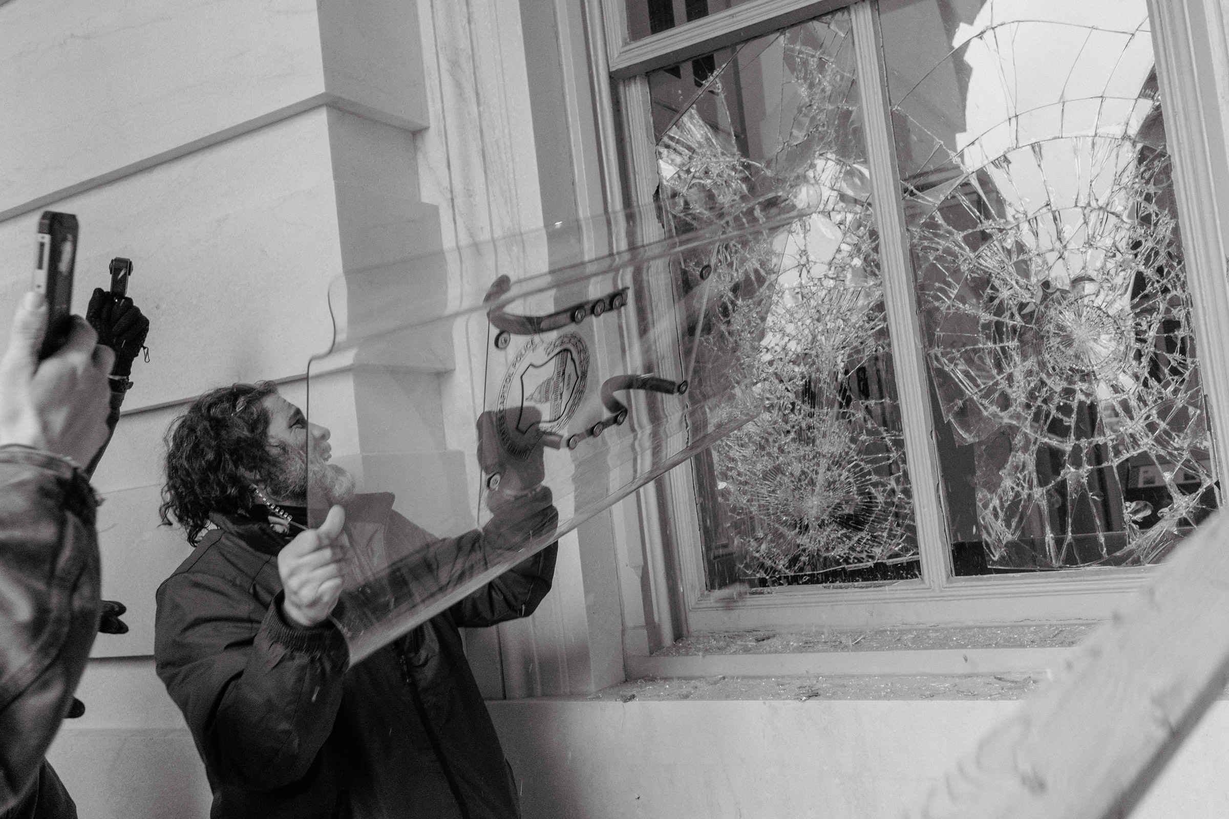 Pro-Trump rioter uses a Capitol Police shield to break through a window at the Capitol building.