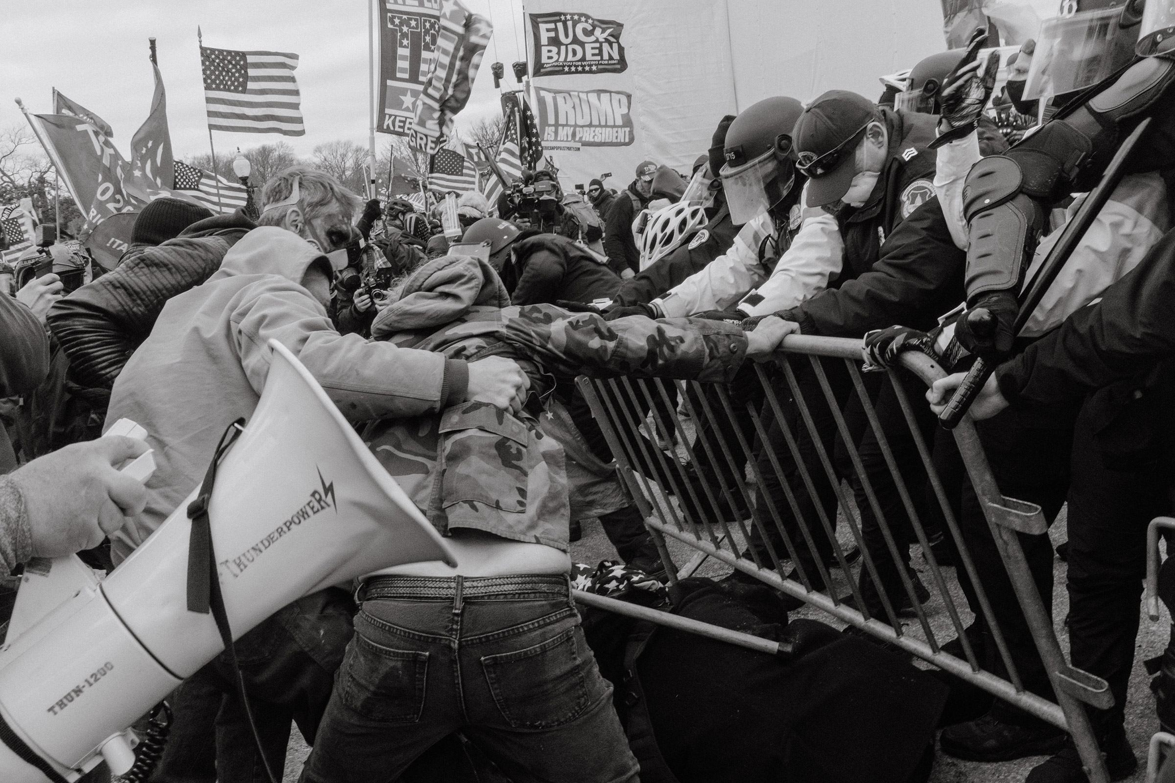 Pro-Trump rioters push through a barrier outside of the Capitol building..