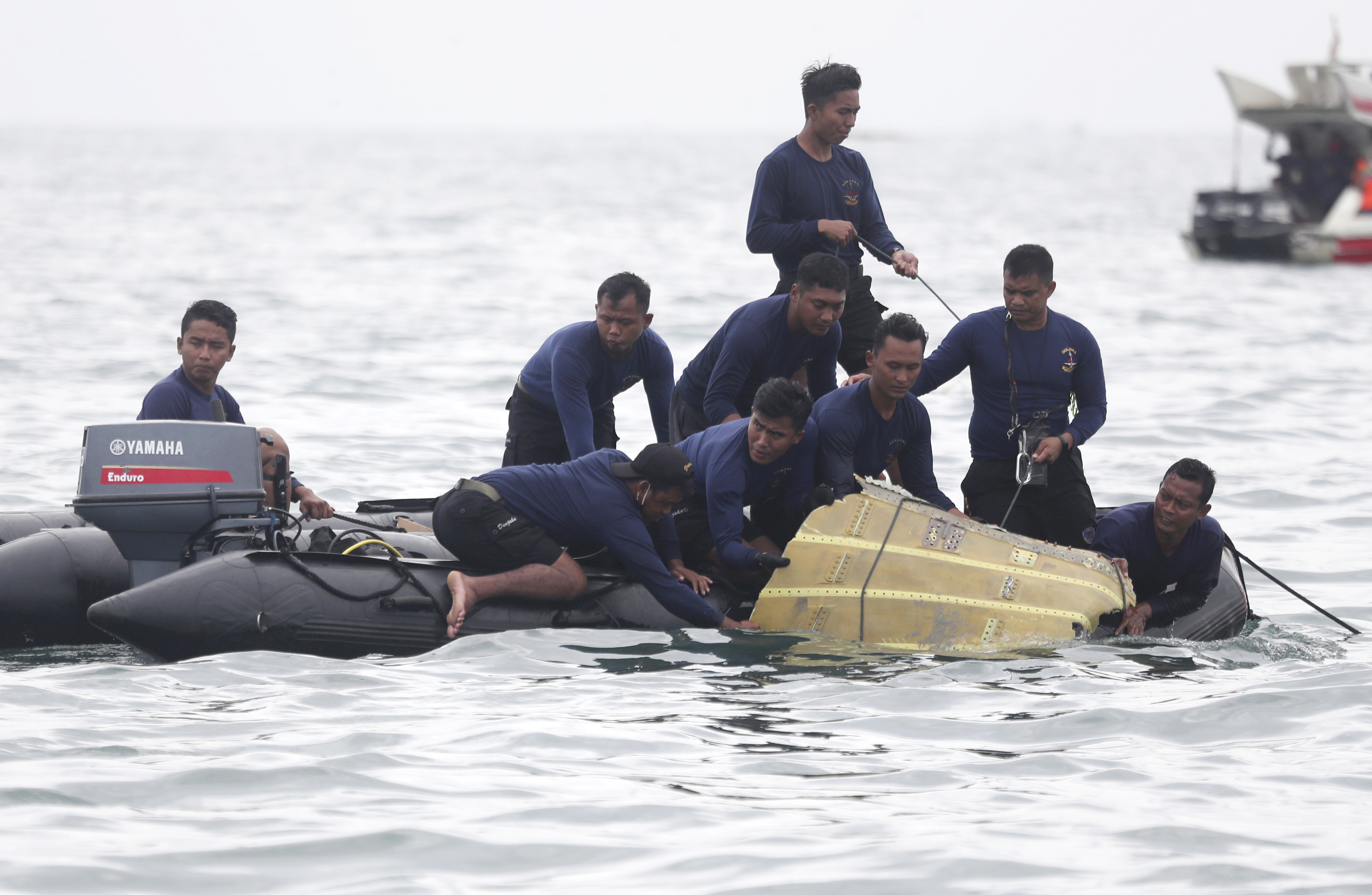 Indonesian Navy divers pull out a part of an airplane out of the water during a search operation for the Sriwijaya Air passenger jet that crashed into the sea near Jakarta, Indonesia, on Jan. 10, 2021.